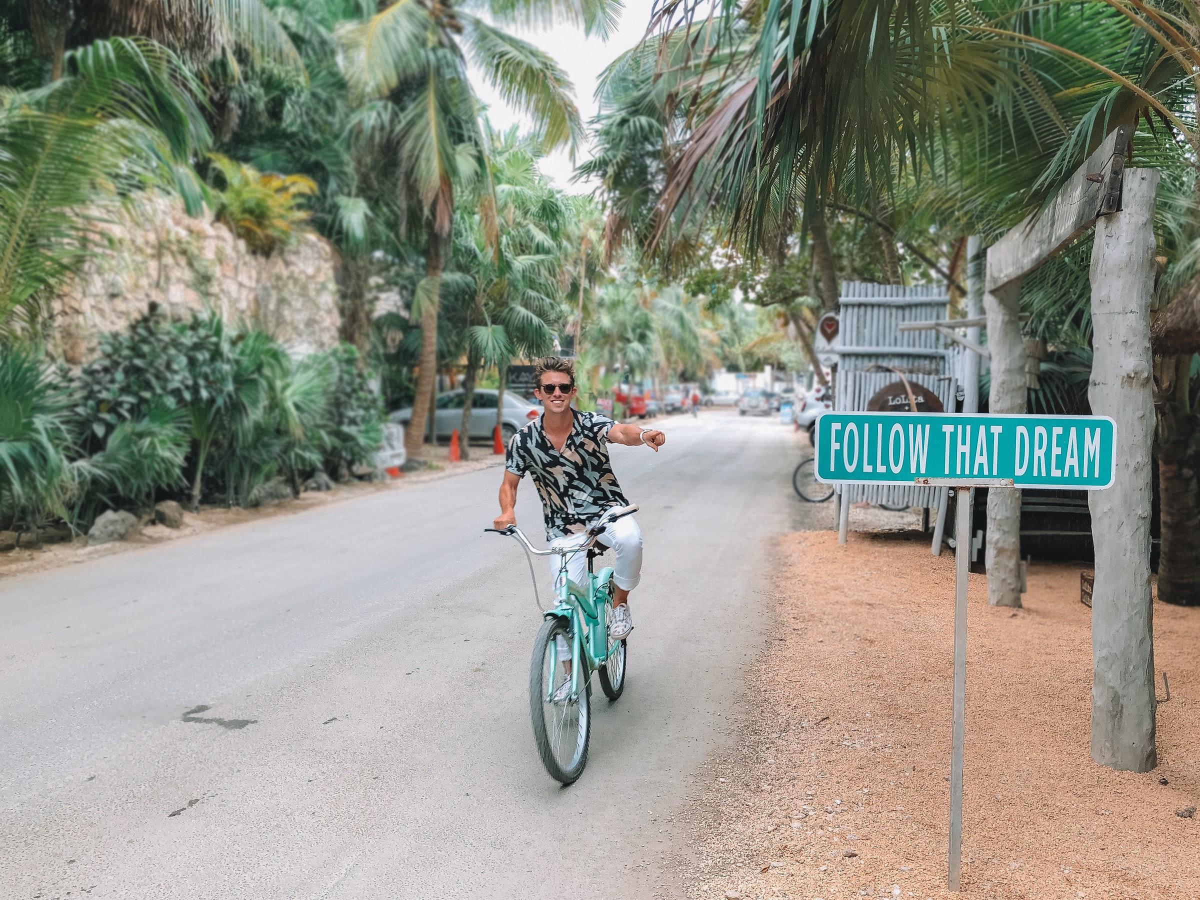 """Man on bike in tropical location pointing to a street sign that says, """"Follow That Dream."""""""