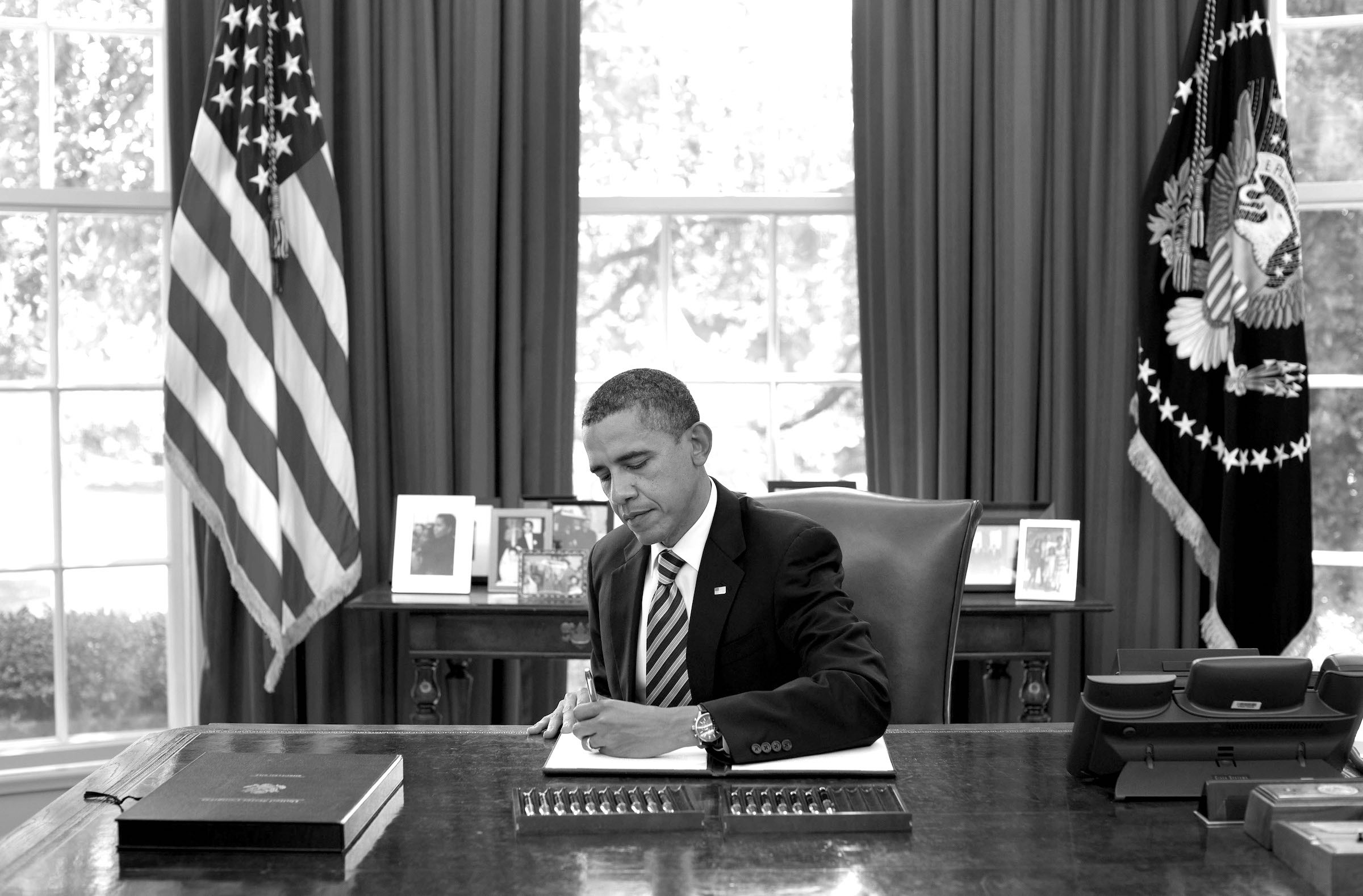 Barack Obama sitting at his desk in the Oval Office, signing a piece of paper.