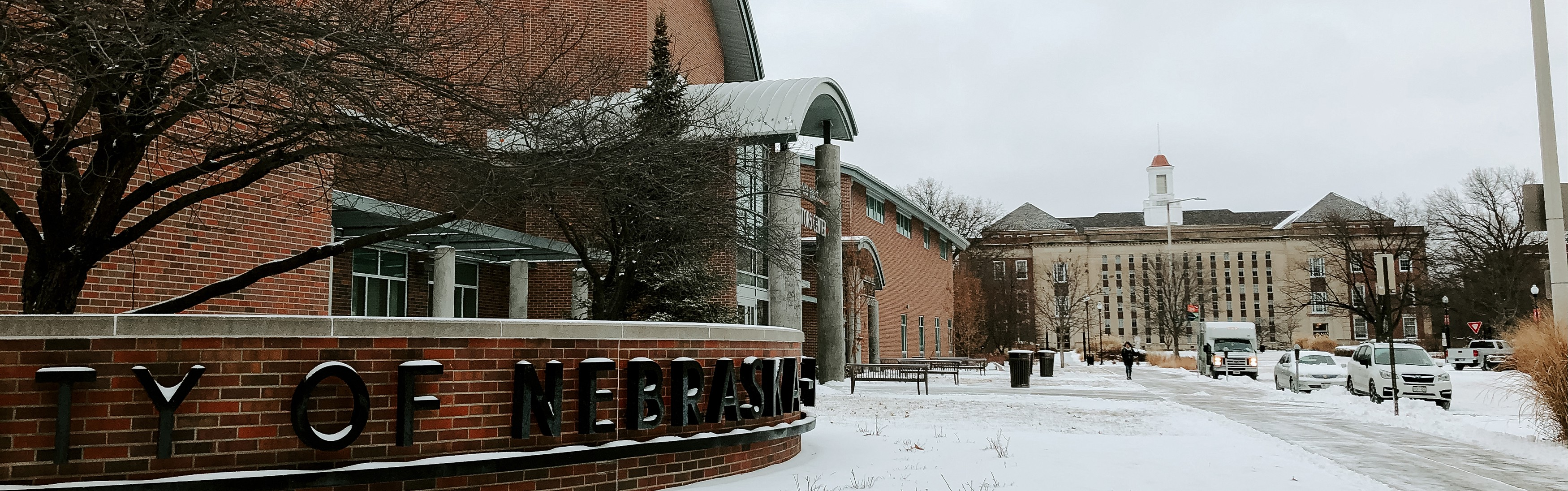 Snow covers the ground surrounding the Visitors Center with Love Library in the distance.