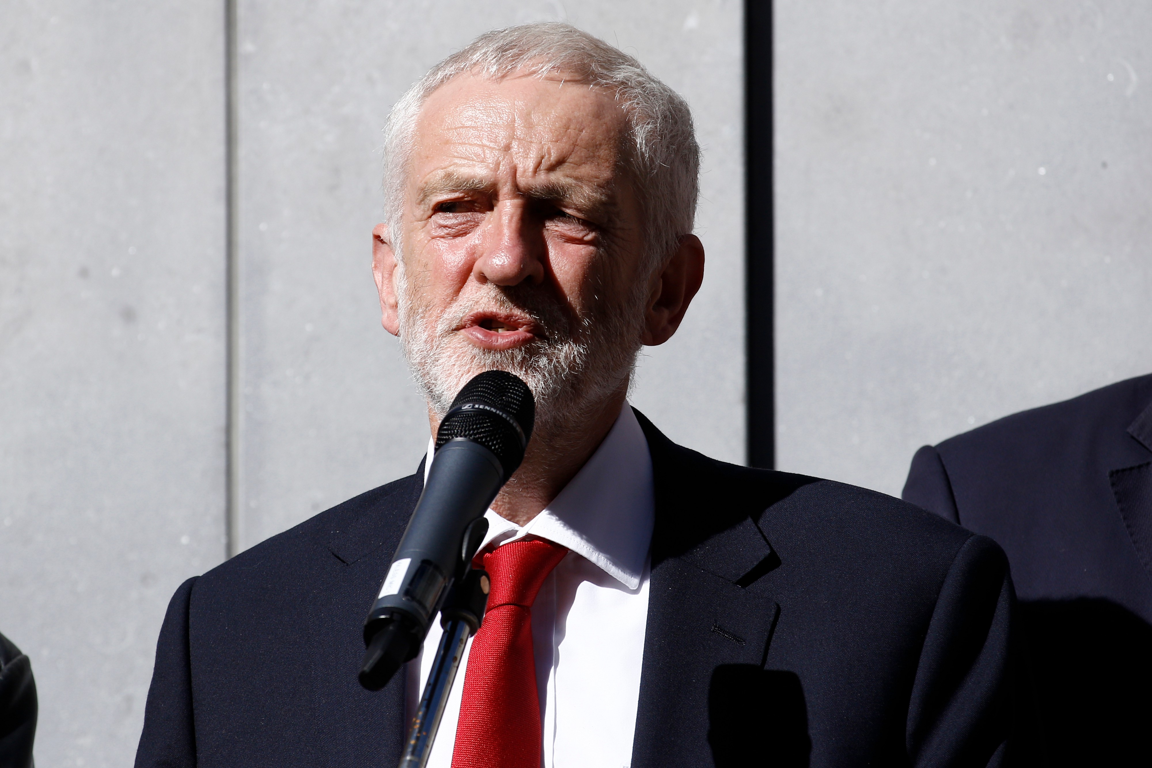 Photo of Jeremy Corbyn wearing a red tie with his black suit jacket and white shirt on while speaking into a mic