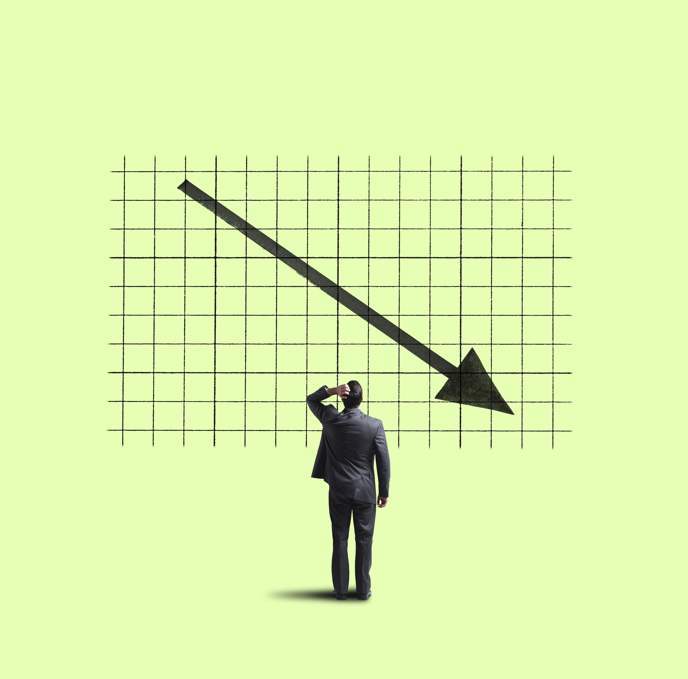 A businessman places his hand on his head as he looks up at a large chart that shows a declining sales or performance trend.