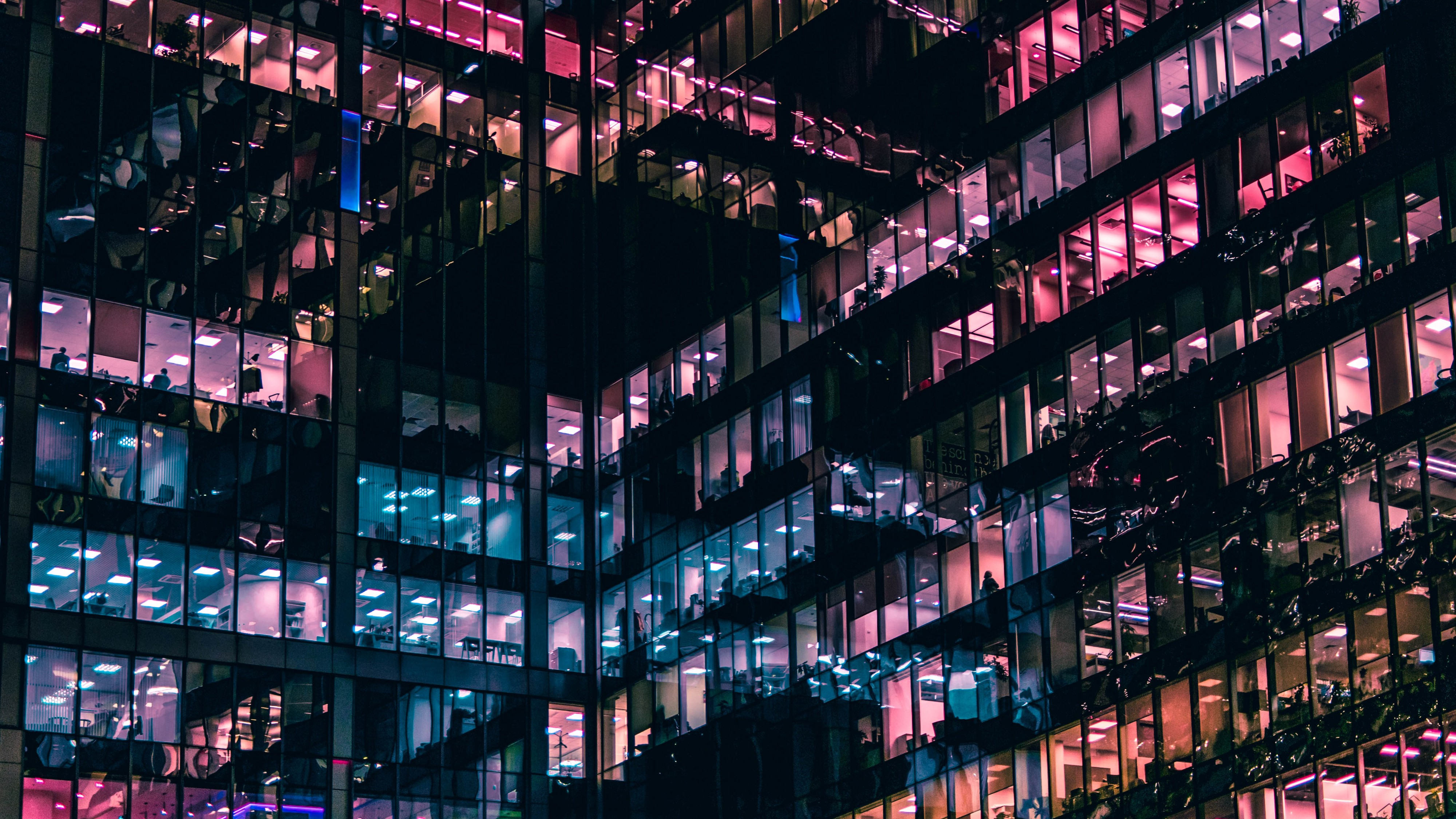 An office building at night with workers in their cubicles