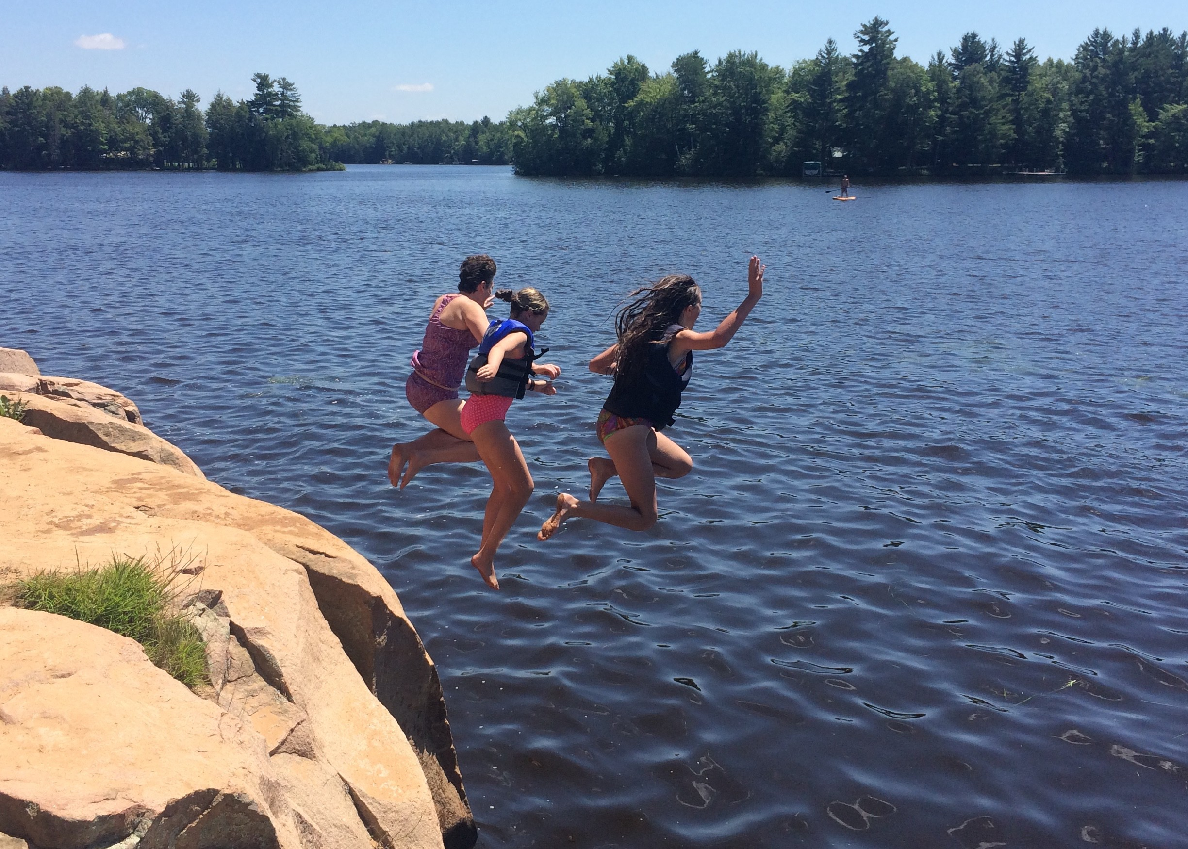 Three people in mid-air, jumping off a large rocky outcropping into a lake.