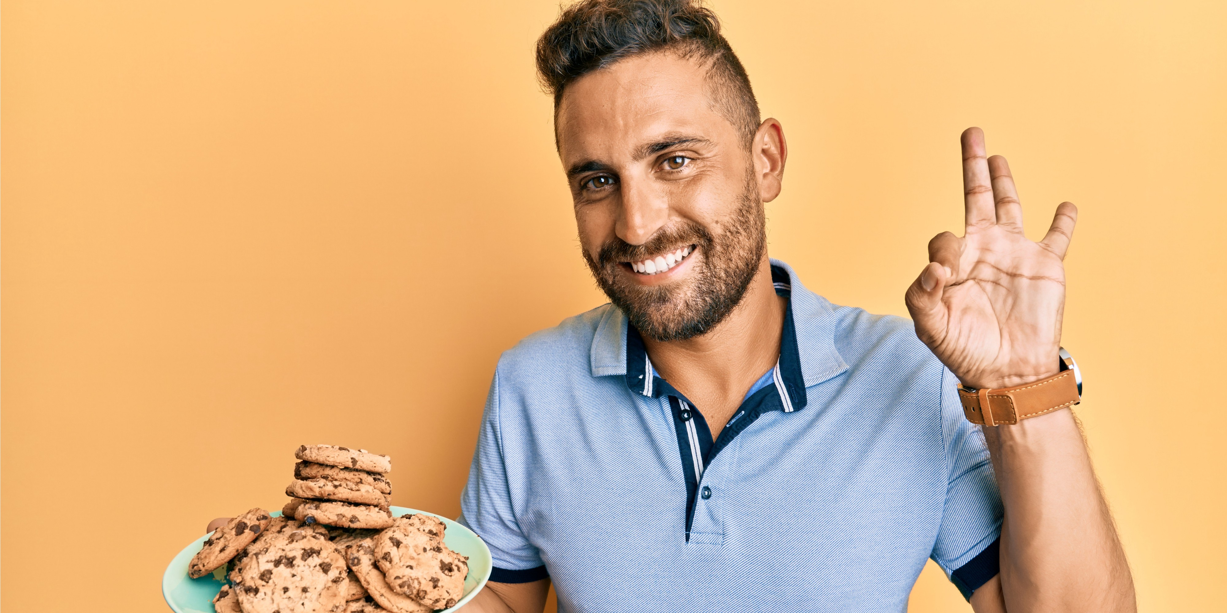 A man holding a plate of chocolate chip cookies. Courtesy of shuterstock.com / Krakenimages.com