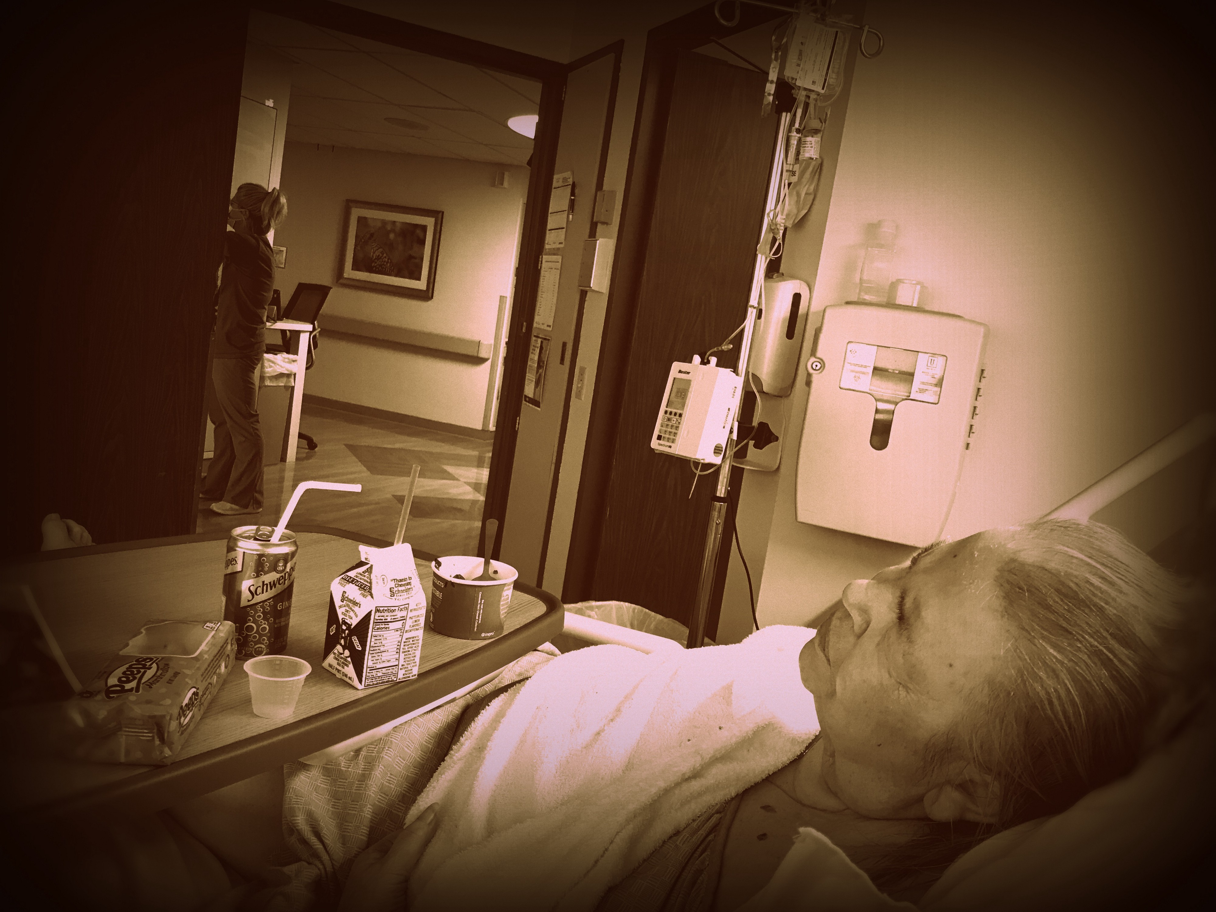 Monochrome photograph of a person laying in a hospital bed a nurse is working in the background