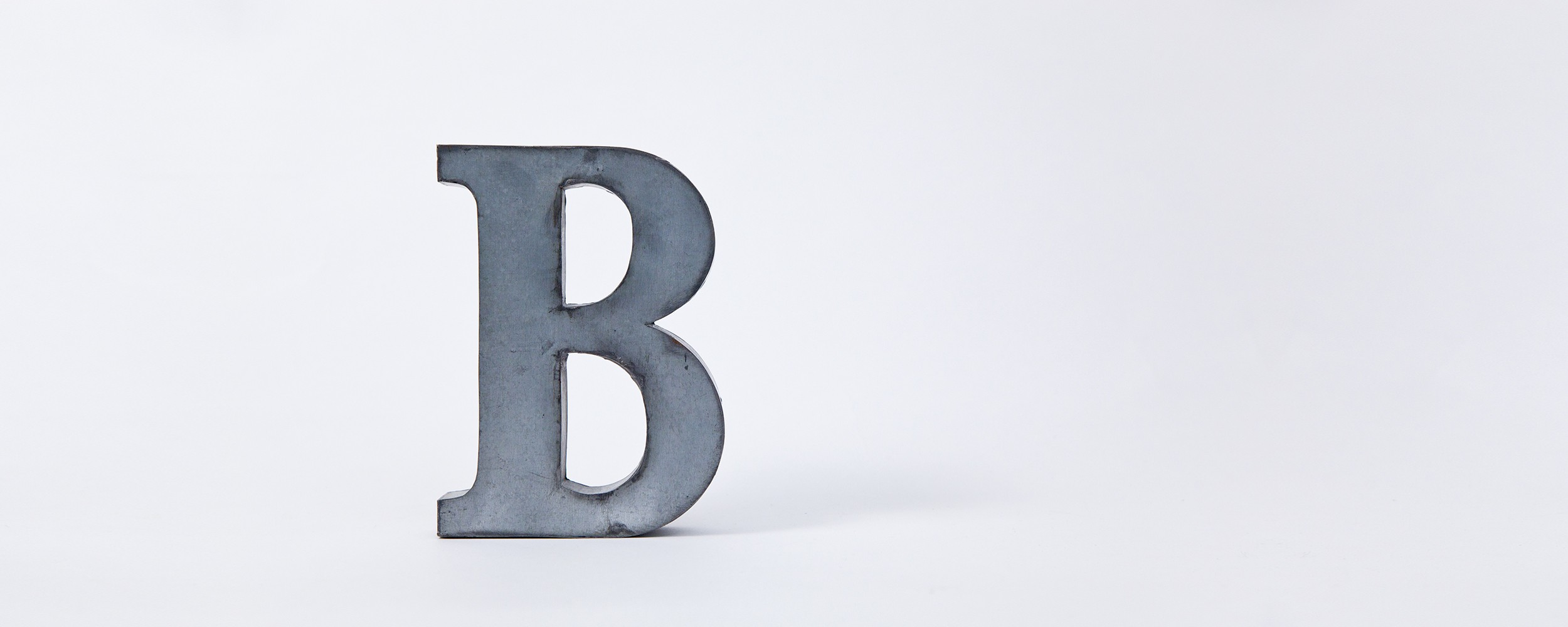 Metal letter B on a grey background