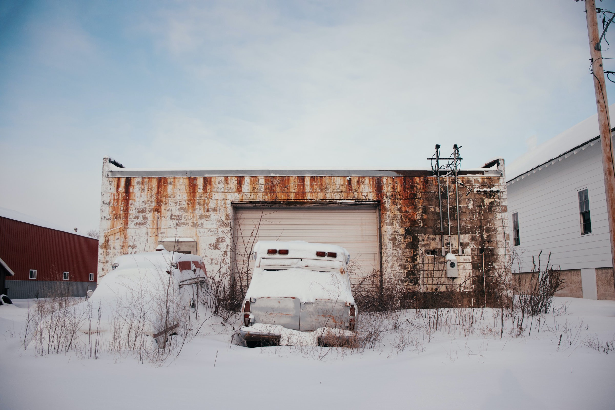 A snow-covered scene with a dilapidated garage and broken-down cars near it.