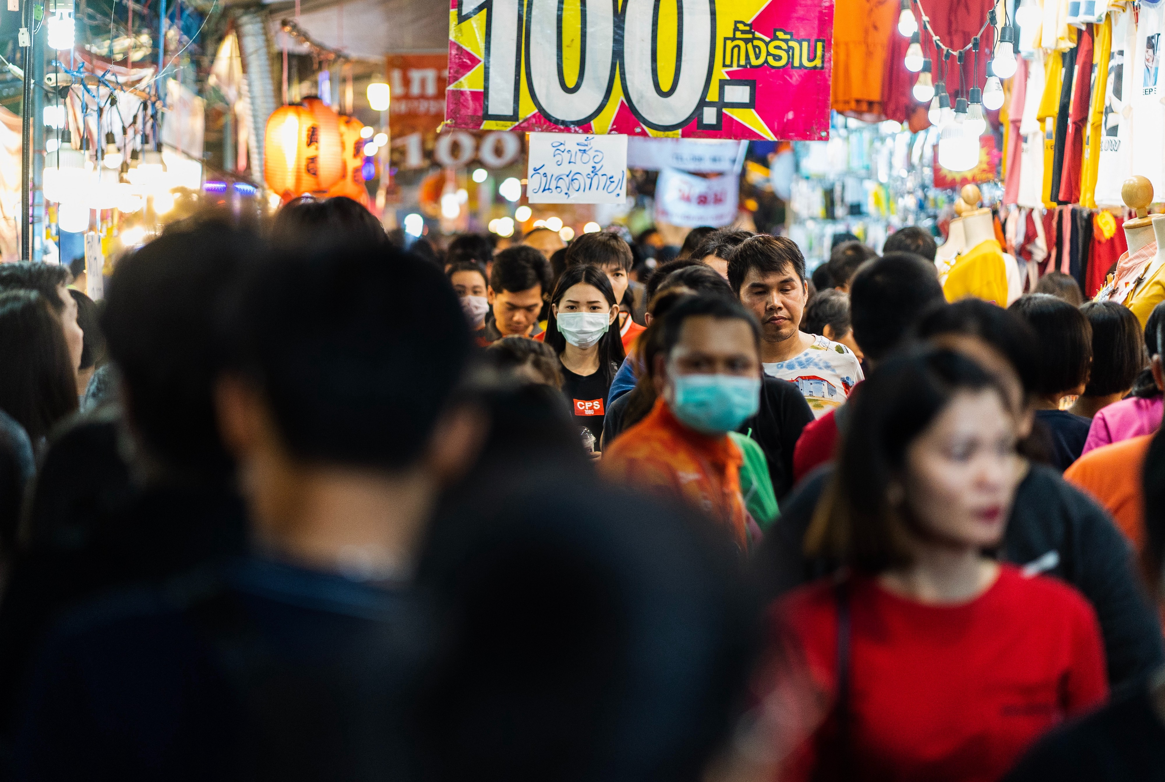 A crowd of people. Some wearing masks