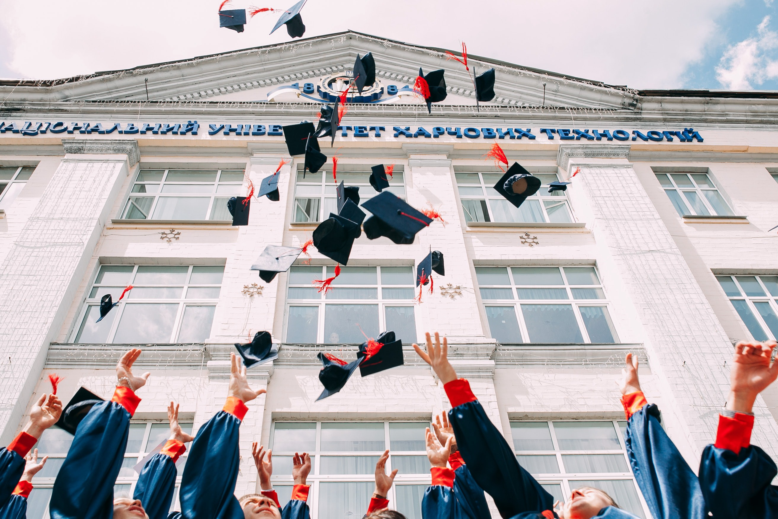 Students throwing their graduation caps in the air.