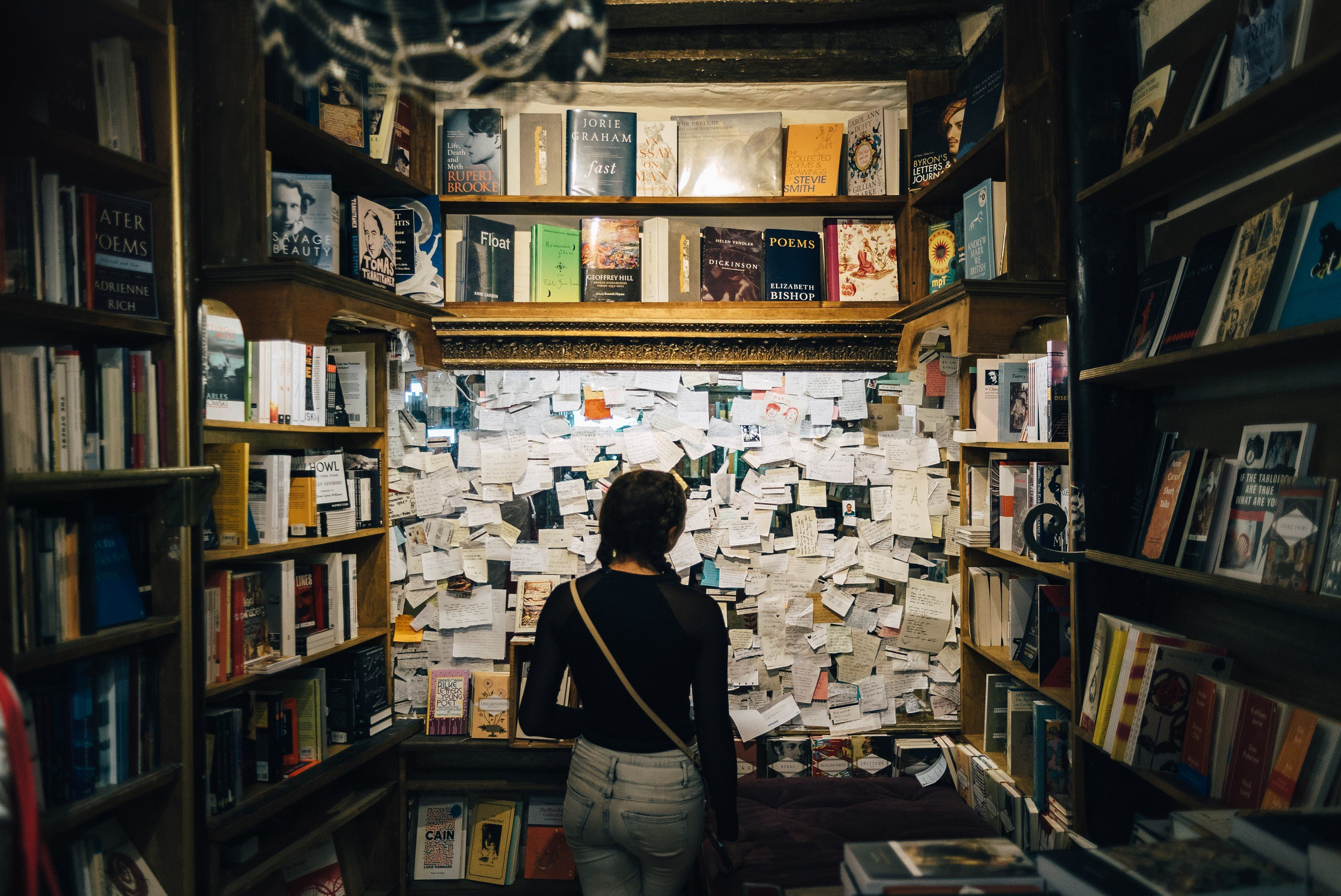 Woman in front of cluttered board in bookstore poetry section