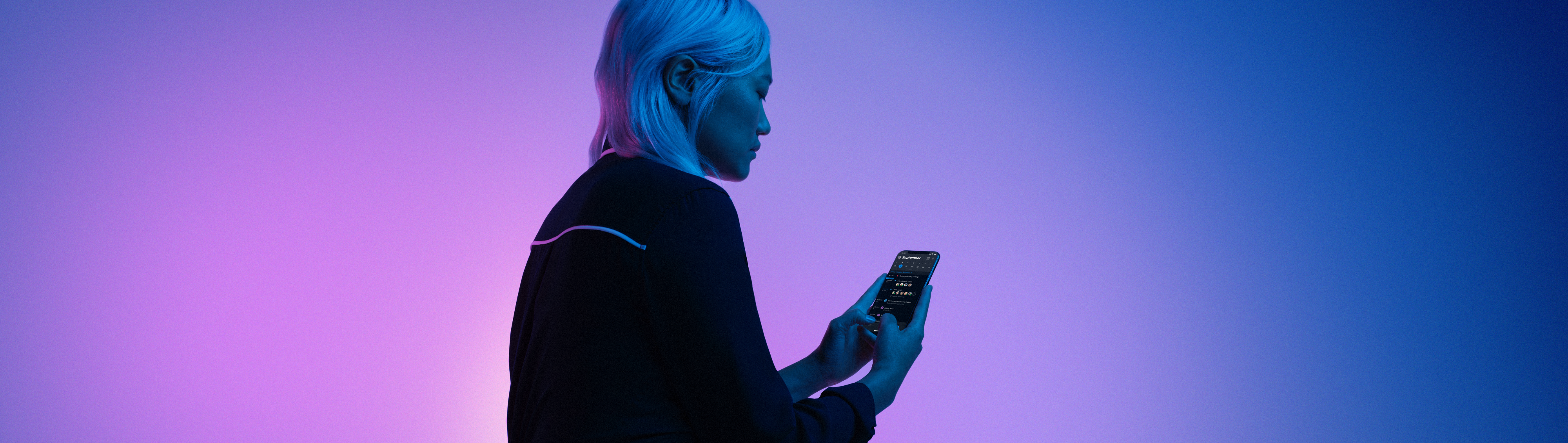 A woman holding a cell phone with Dark Mode enabled.