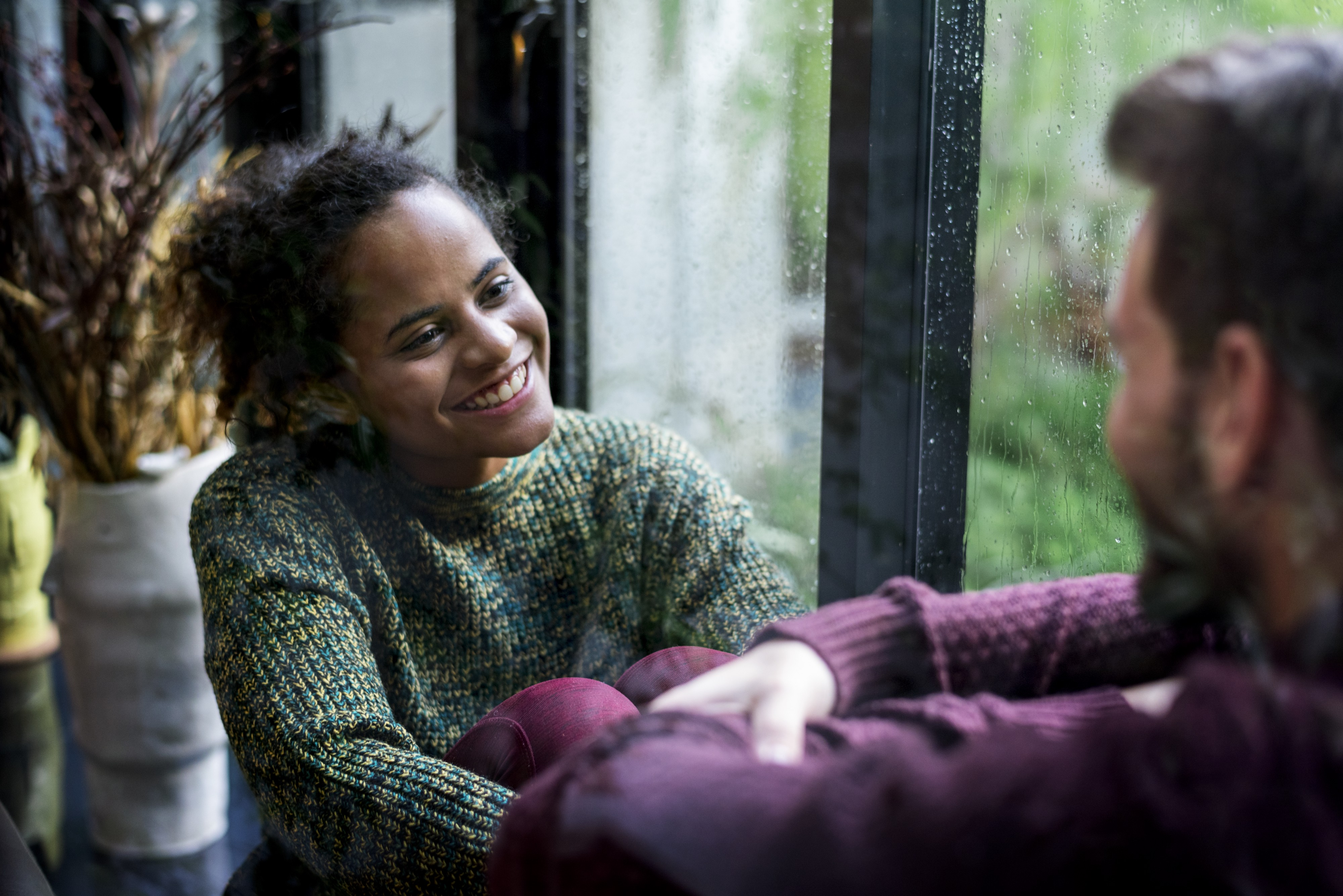 A couple talks happily in a window on a rainy day.