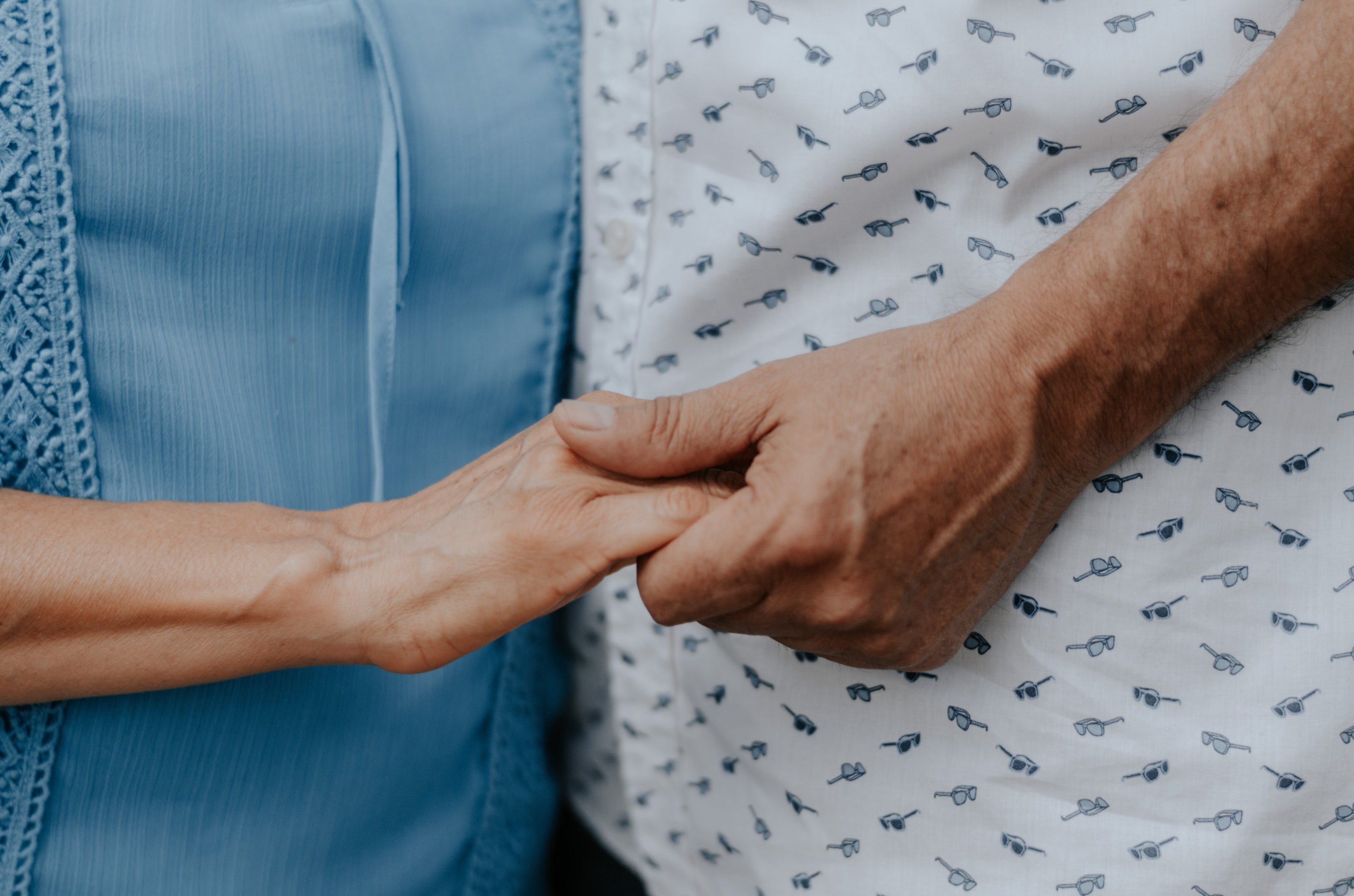 Two elderly people holding hands.