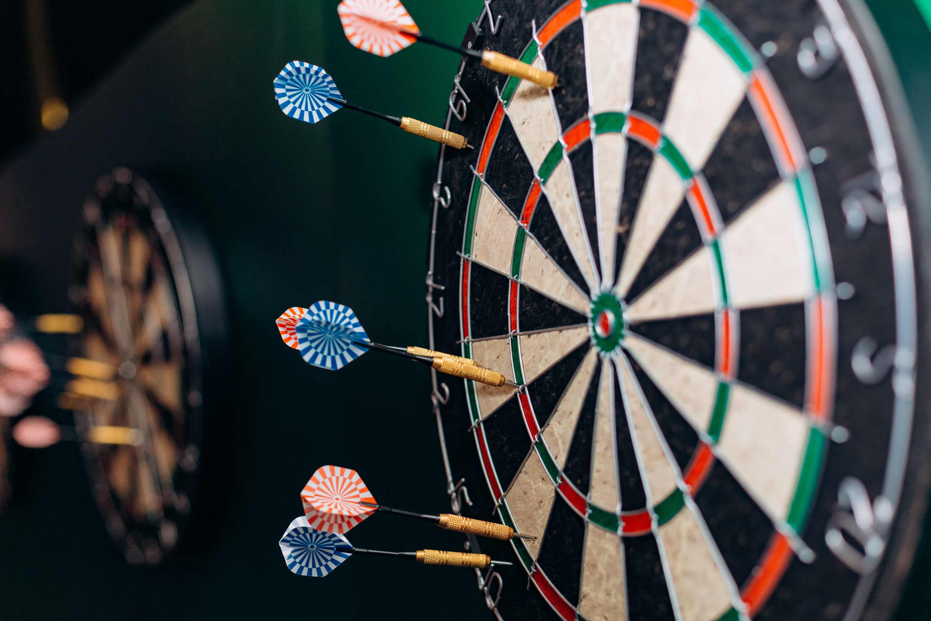 Dart board with darts sticking into the outer circle—no bullseye hits