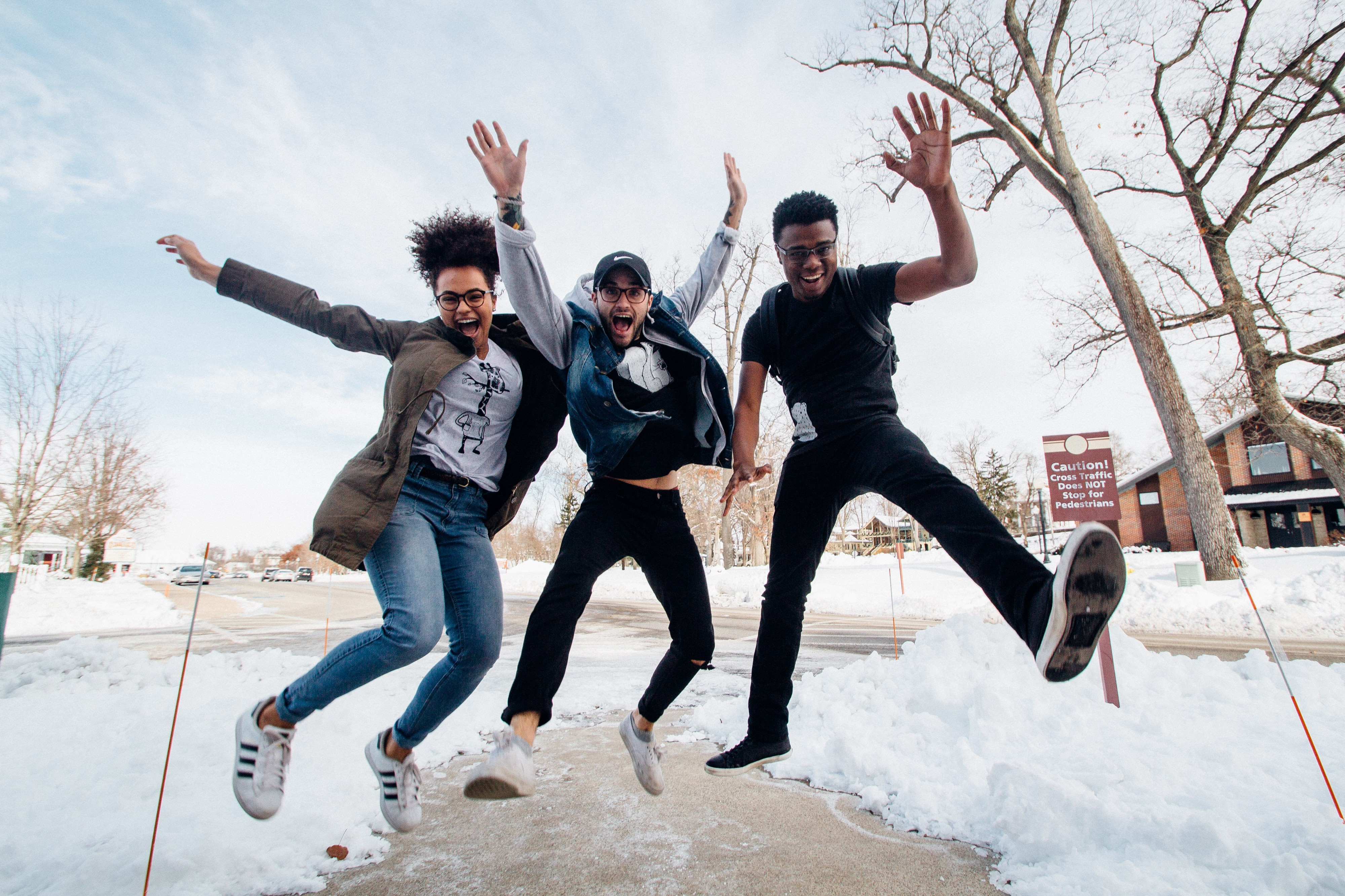 Photo of three men jumping on ground near bare trees during daytime. Credit: Zachary Nelson from Unsplash.com
