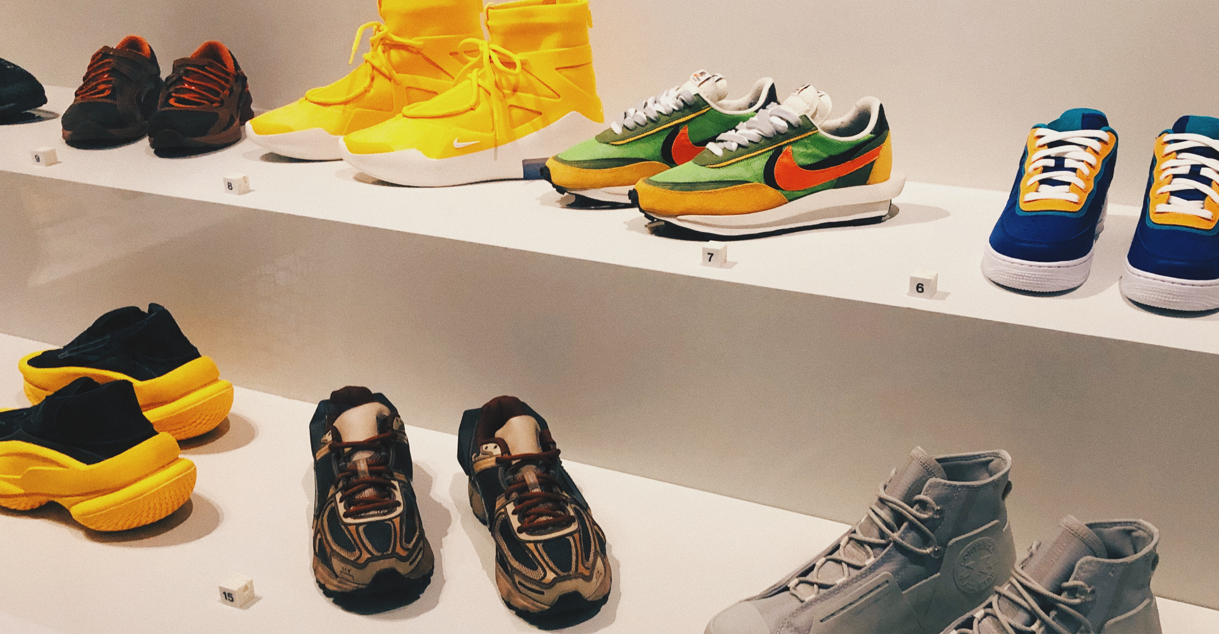 A collection of special edition, colourful sneakers in a cabinet space.