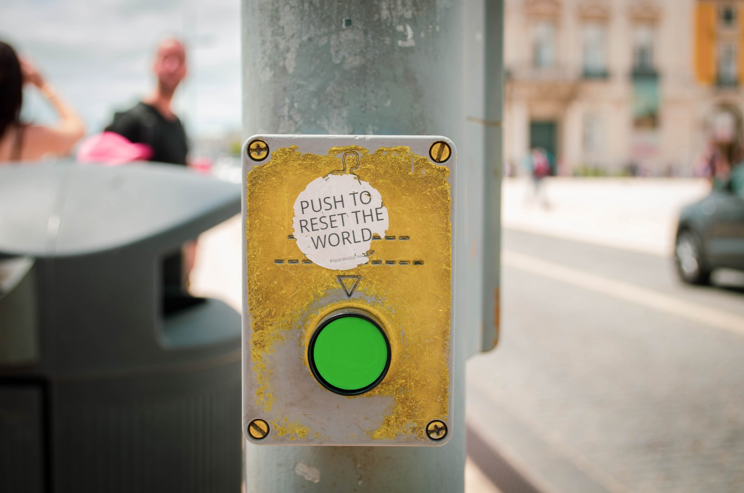 "A green street crosswalk button for pedestrians, with a sticker placed above it that reads ""Push to reset the world""."