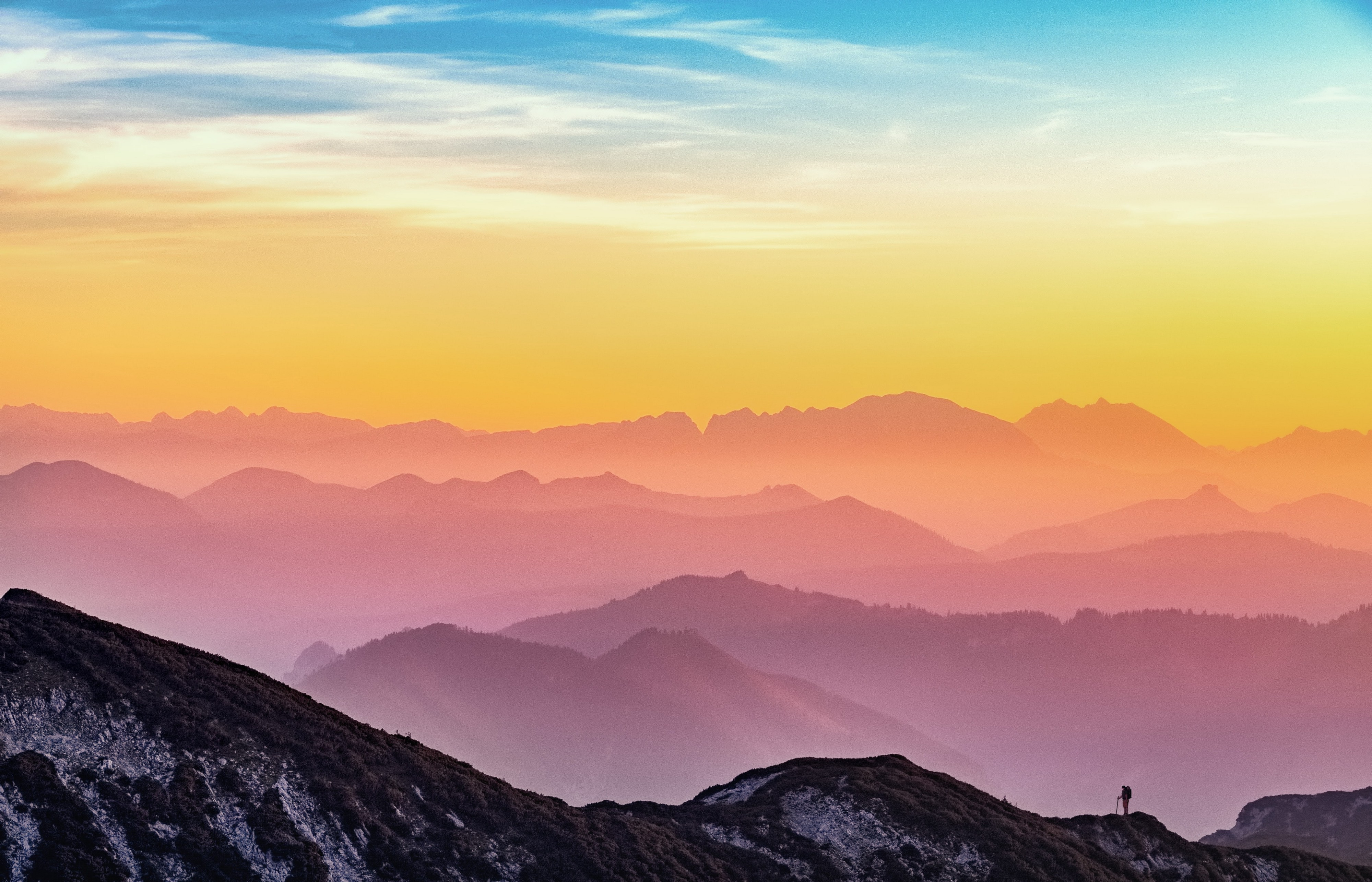 Man standing on top of mountain with colorful sunset behind.