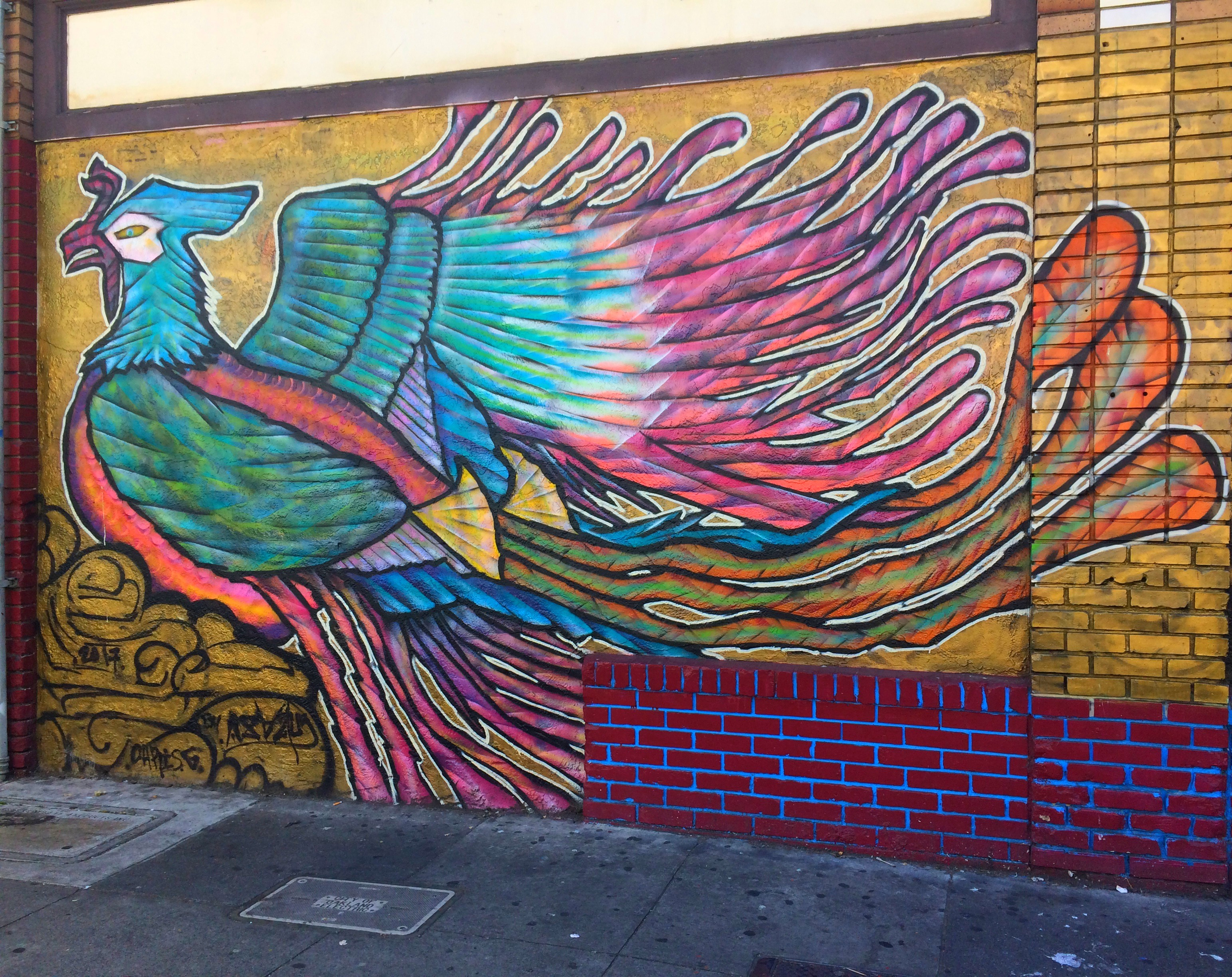 A red-brick wall painted over with a large mural of a parrot with long, sweeping wings and tail feathers on a yellow background.