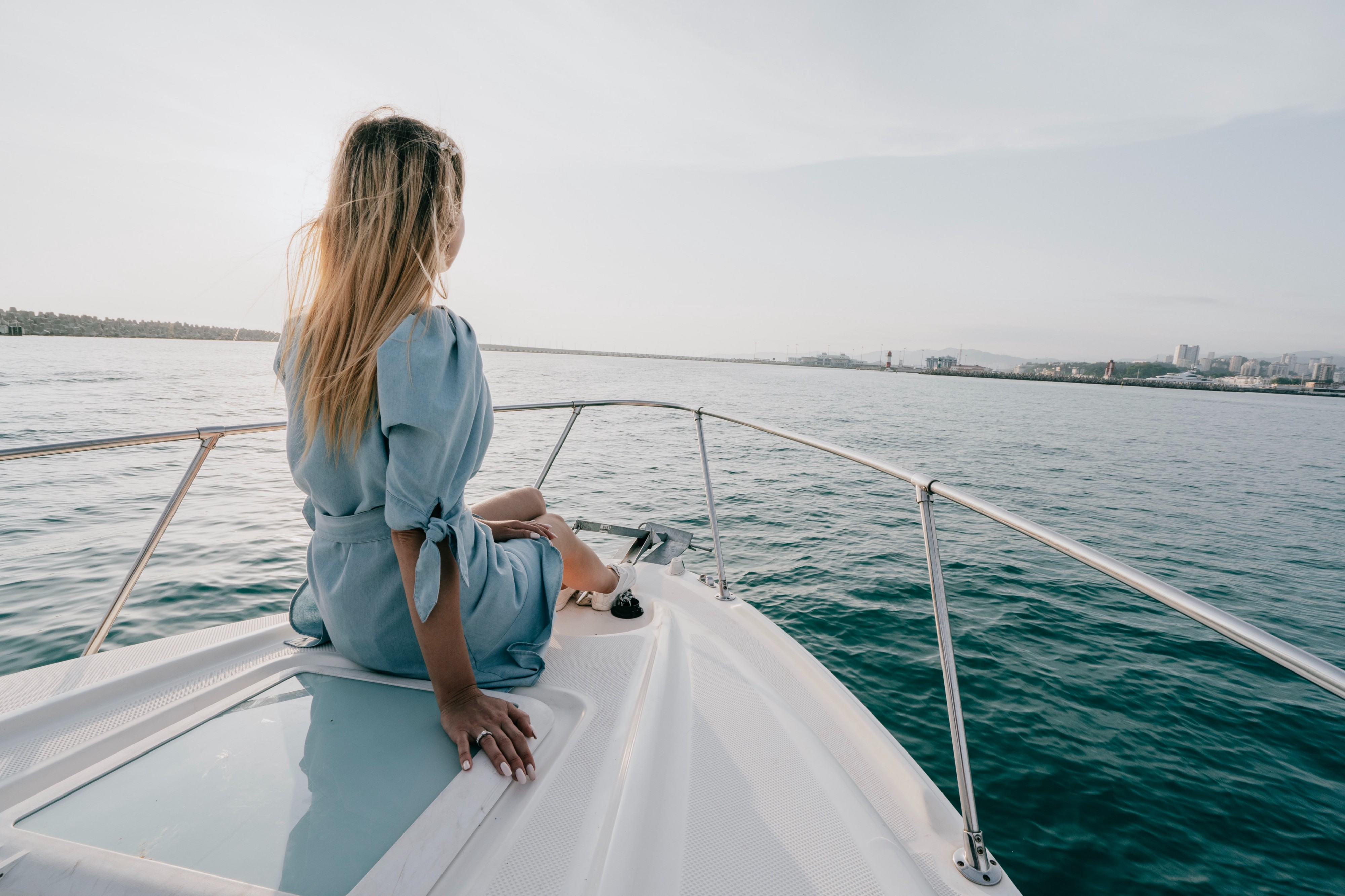 Woman in a blue dress sitting on the bow of a boat at sea during daytime.