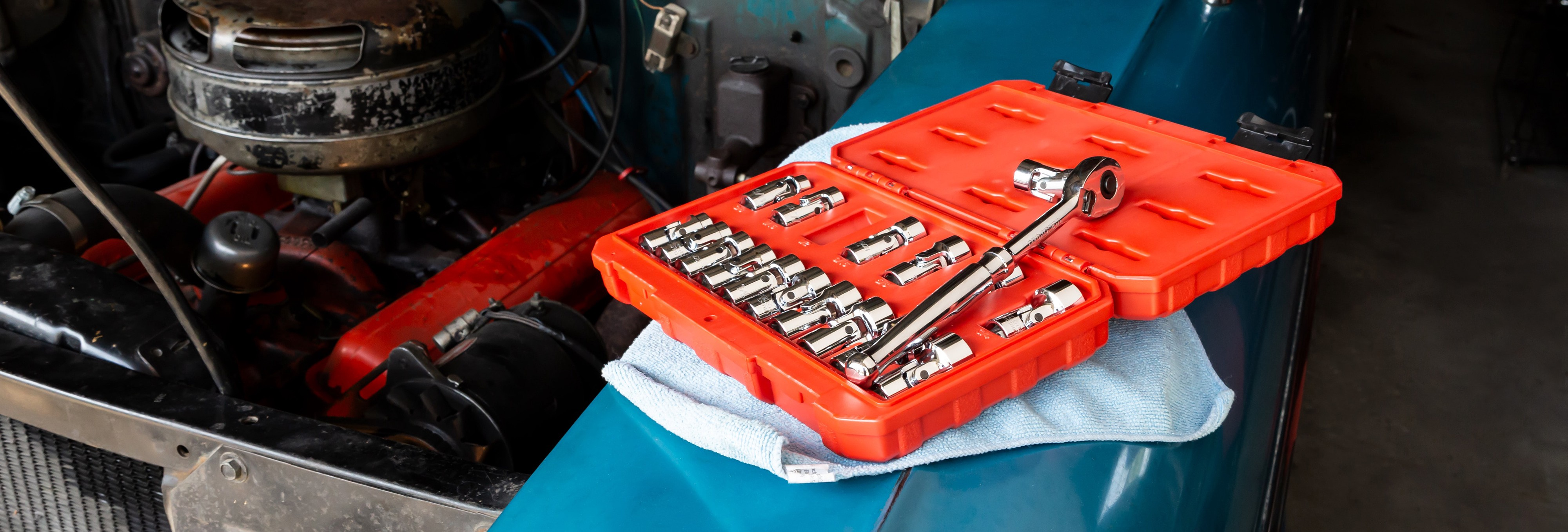 A toolbox leans on an engine to fix.
