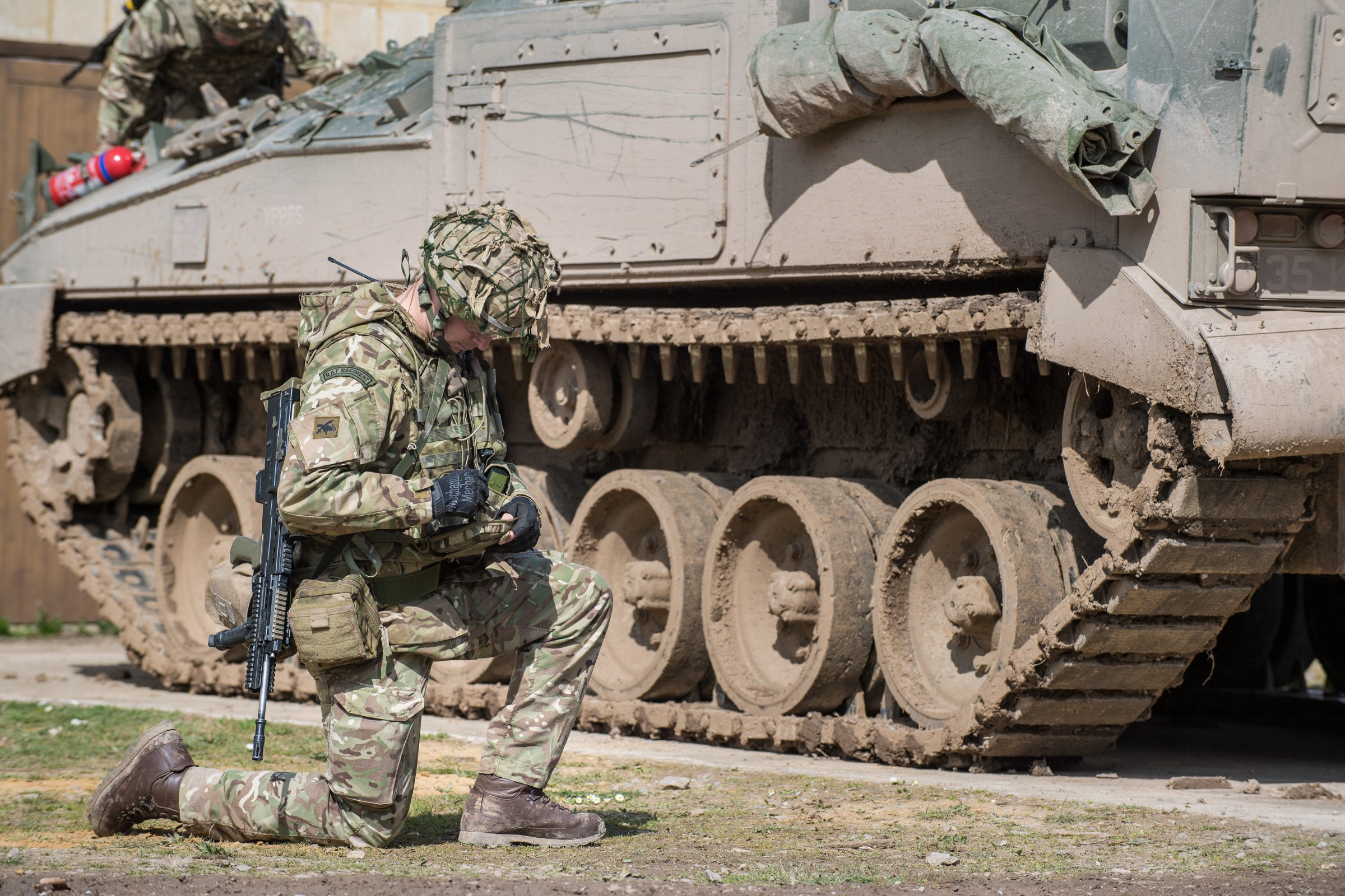 Soldier kneeling down beside an armoured vehicle working with handheld technology to relay information to others in the field