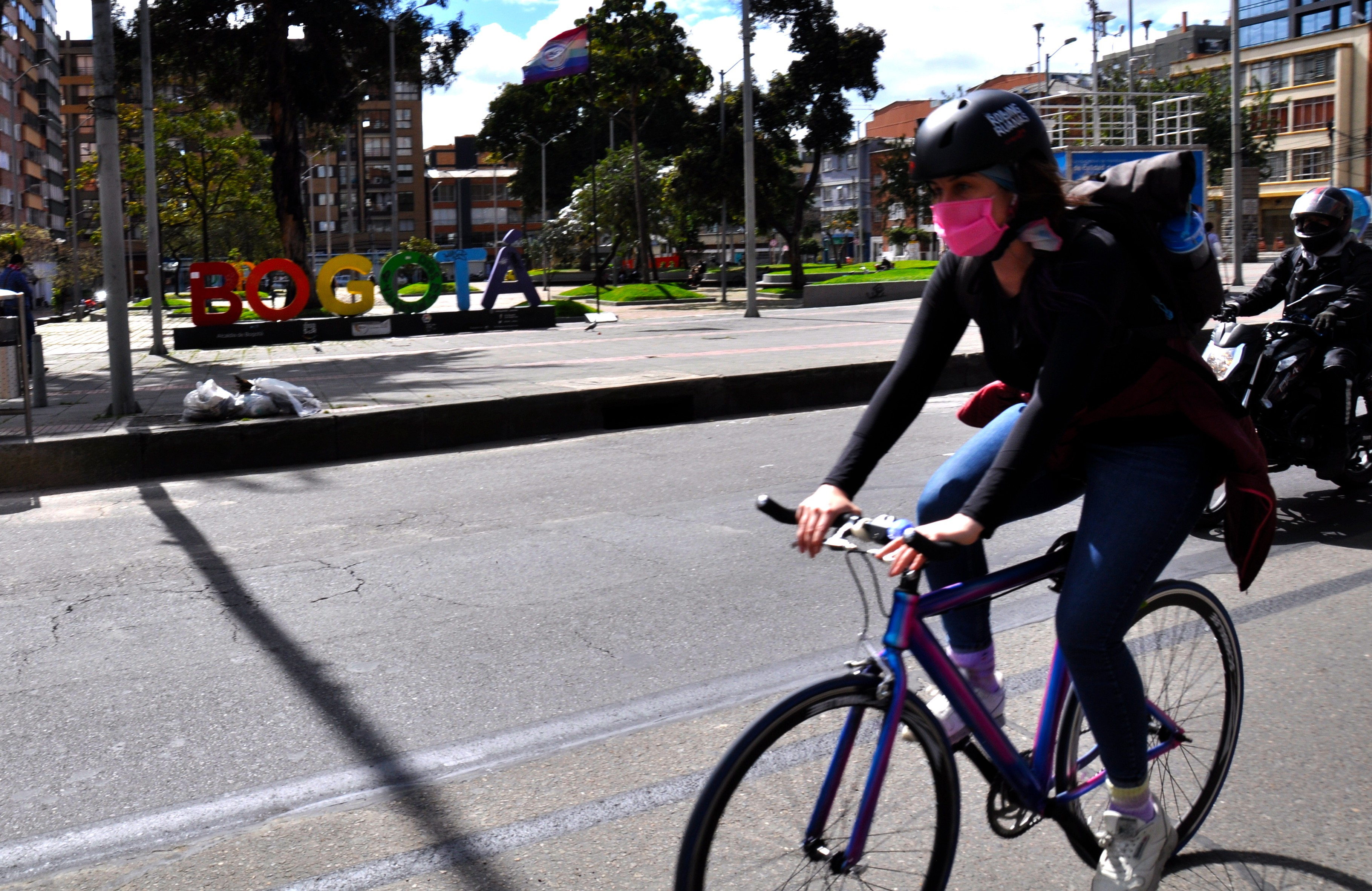 Cyclist cycling past a sign in the city of Bogota