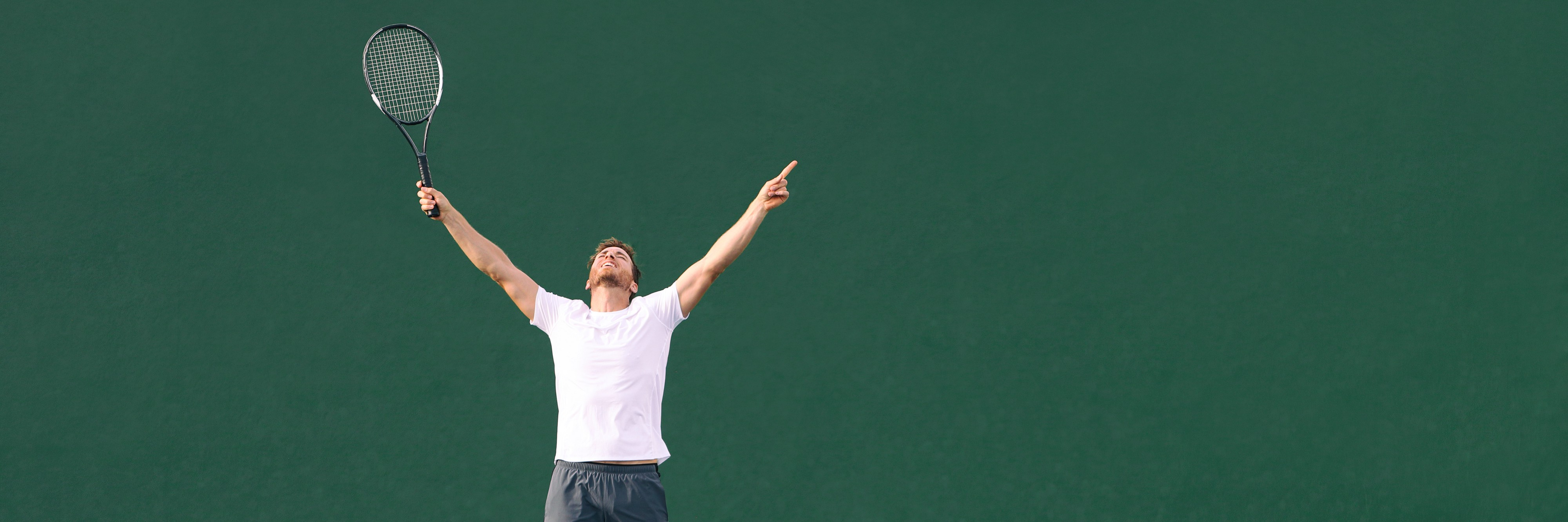 Tennis player raising his arms in victory.