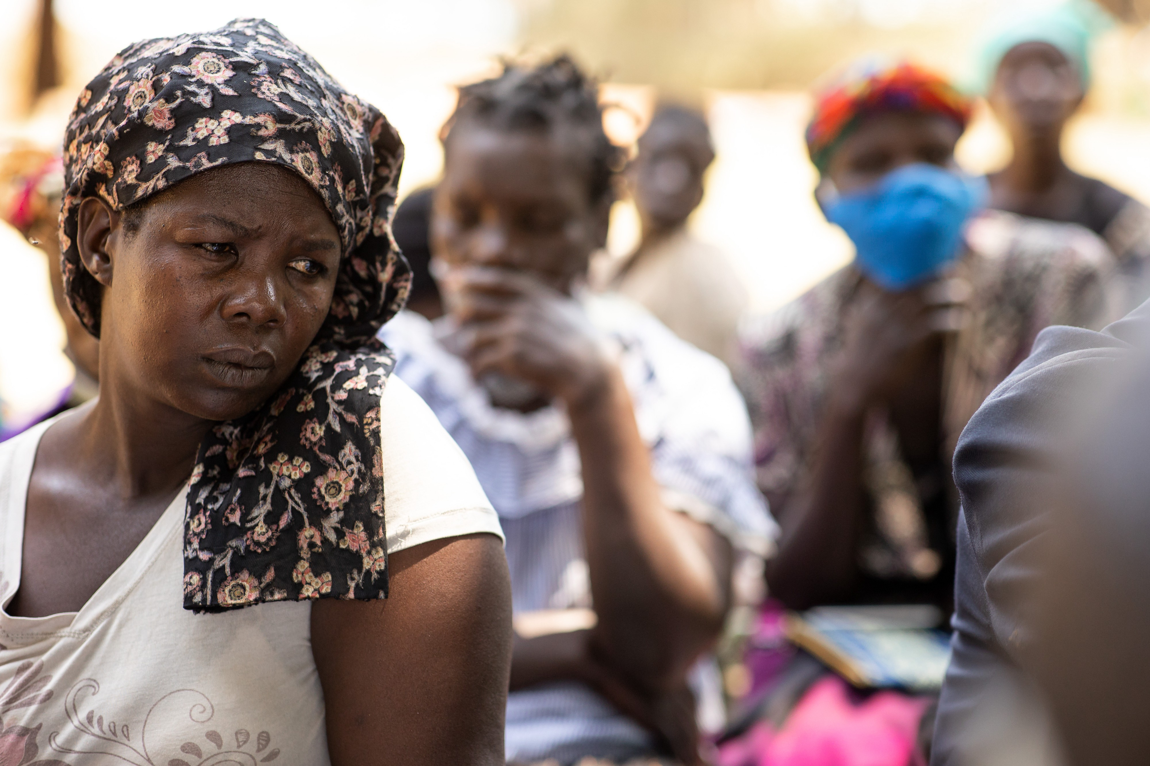 A Ugandan woman looks mournfully to her left, while sitting with a group of people outdoors.