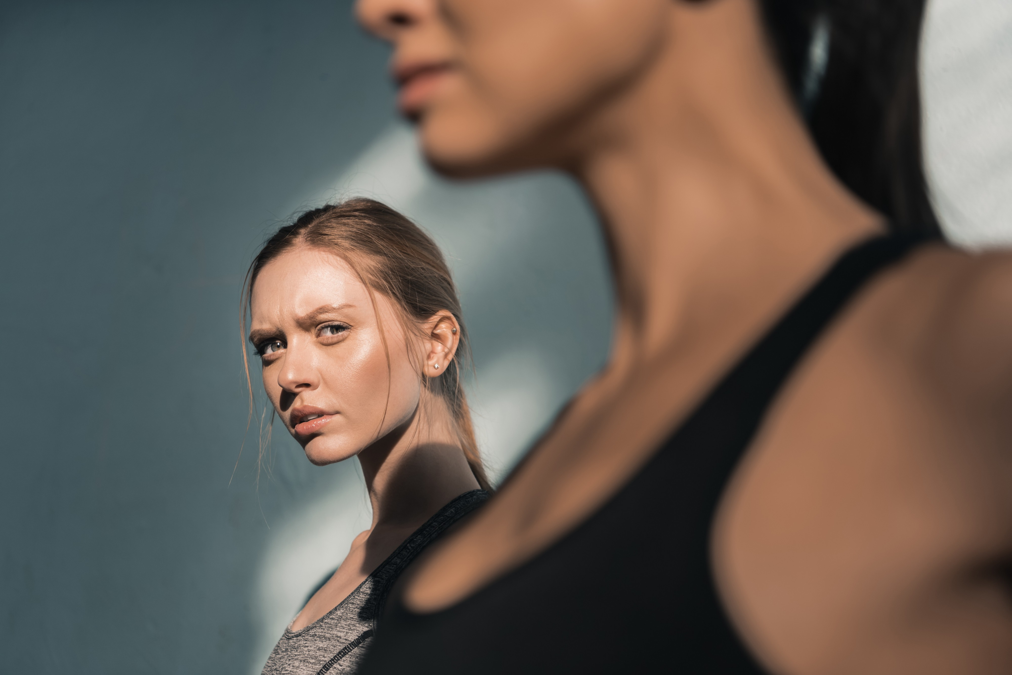 A woman stares suspiciously at her friend as they work out together.