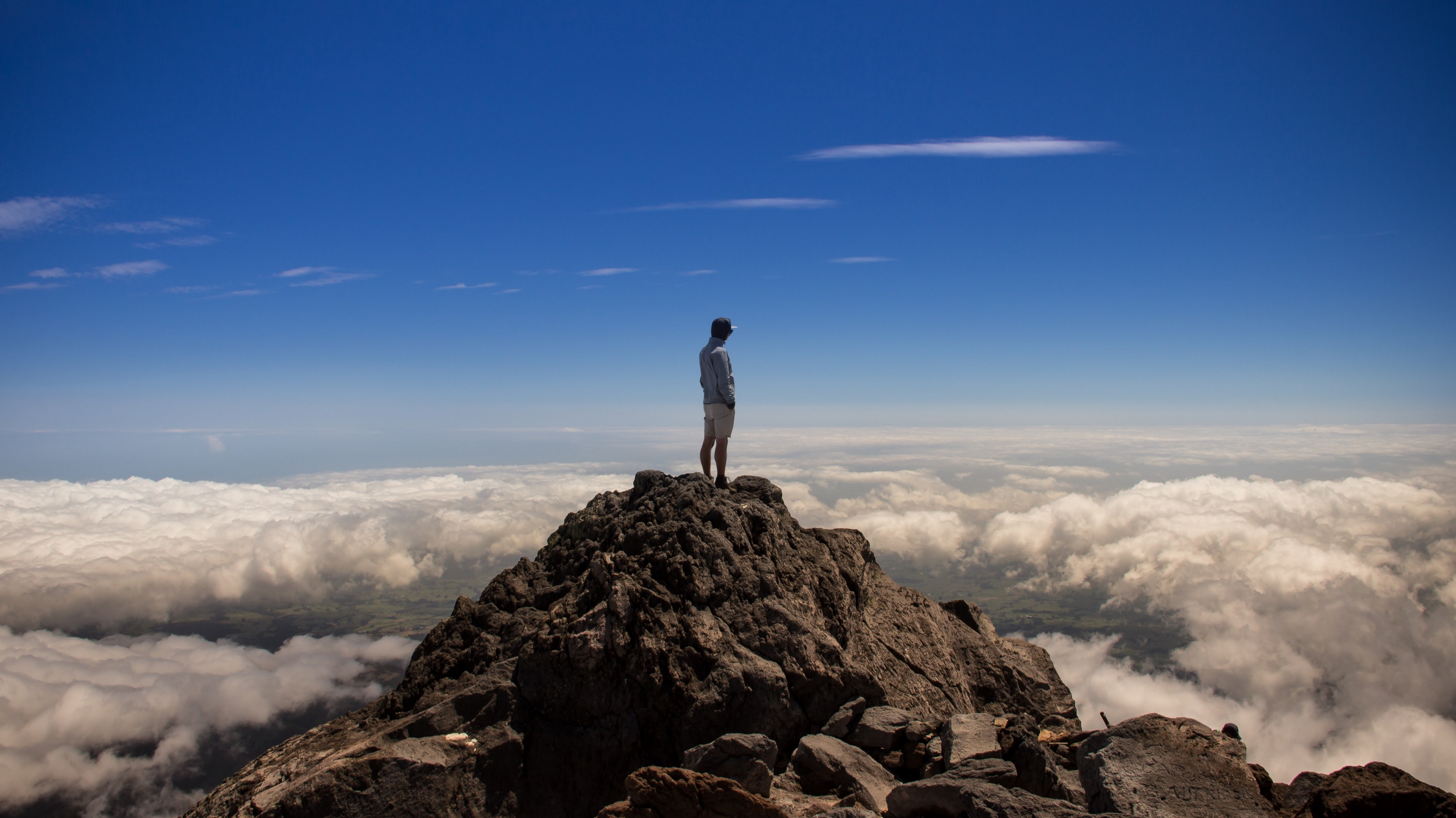 Man standing on mountaintop looking out over the clouds.