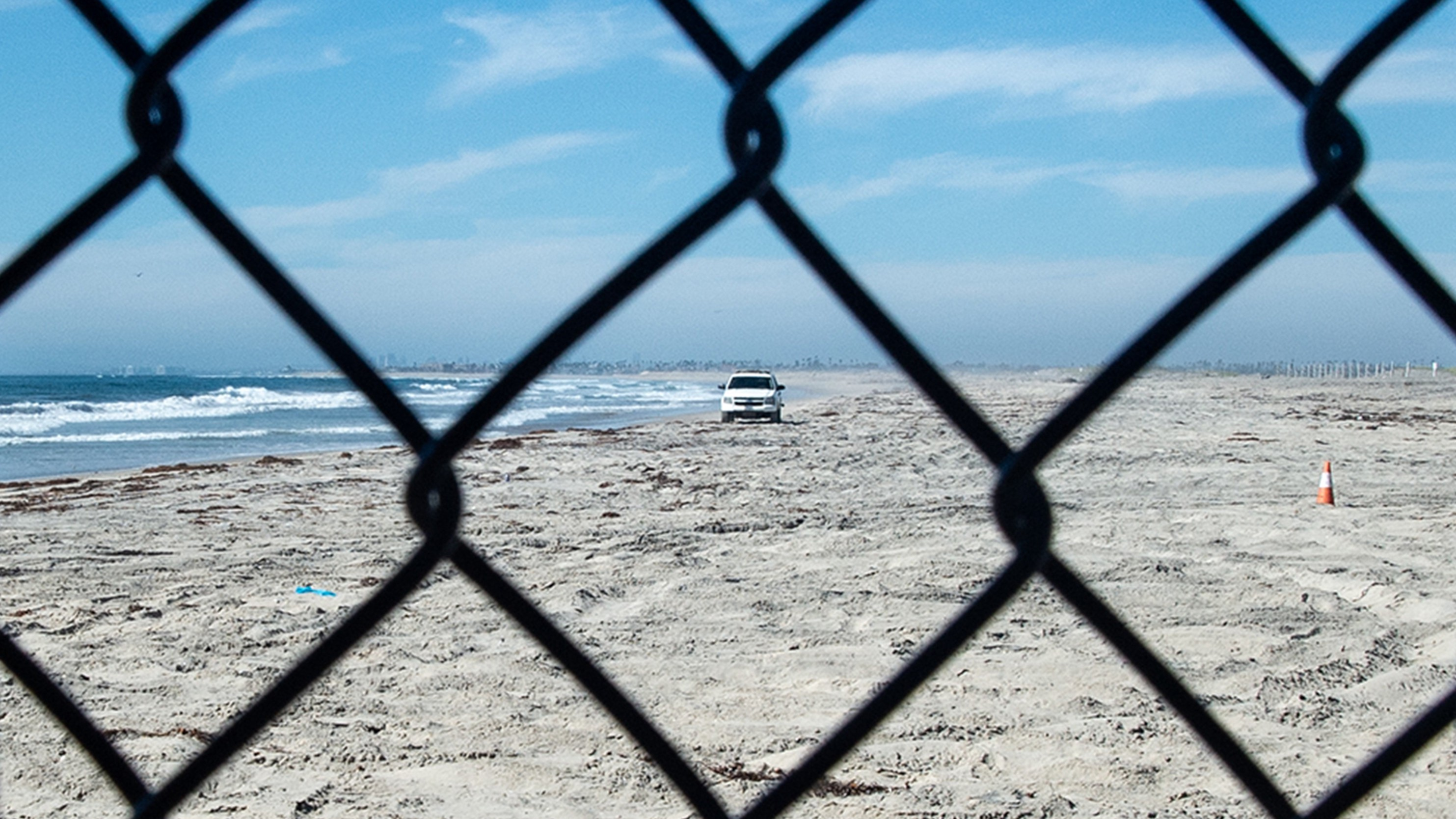 The United States seen through fencing at the border of the U.S. and Tijuana, Mexico. A Border Patrol vehicle can be seen through the chain-link fence. Photo by Robert Stribley.