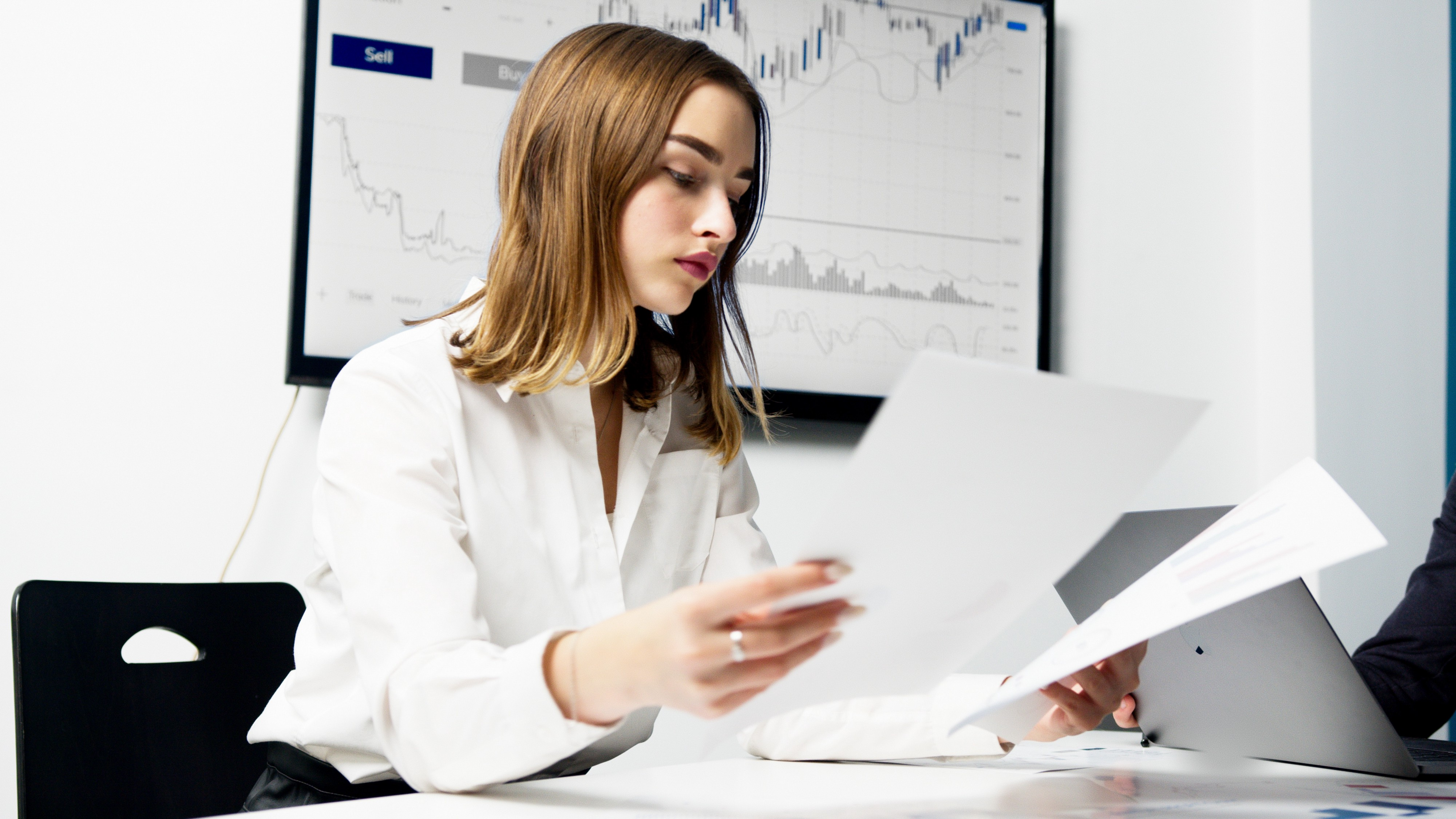 Woman analyzing papers with stock market chart behind her