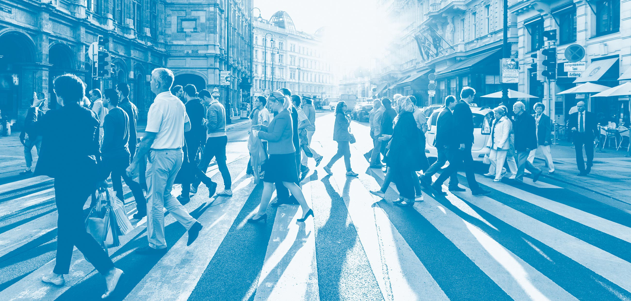 Photograph shows a lot of different types of people walking across a main road crossing using a light blue duotone