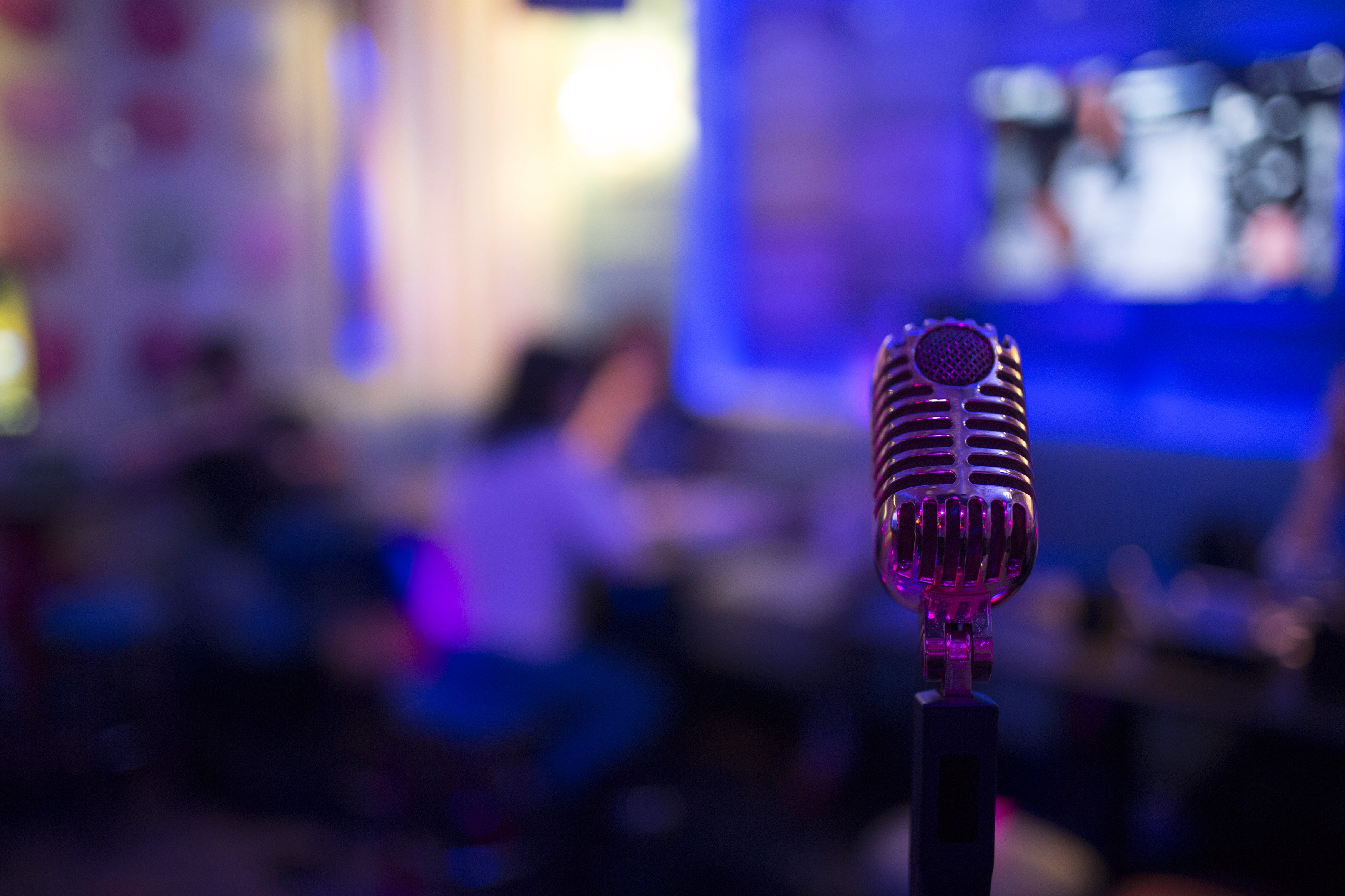 An old-fashion microphone is in the foreground, behind is an office bathed in blue light.