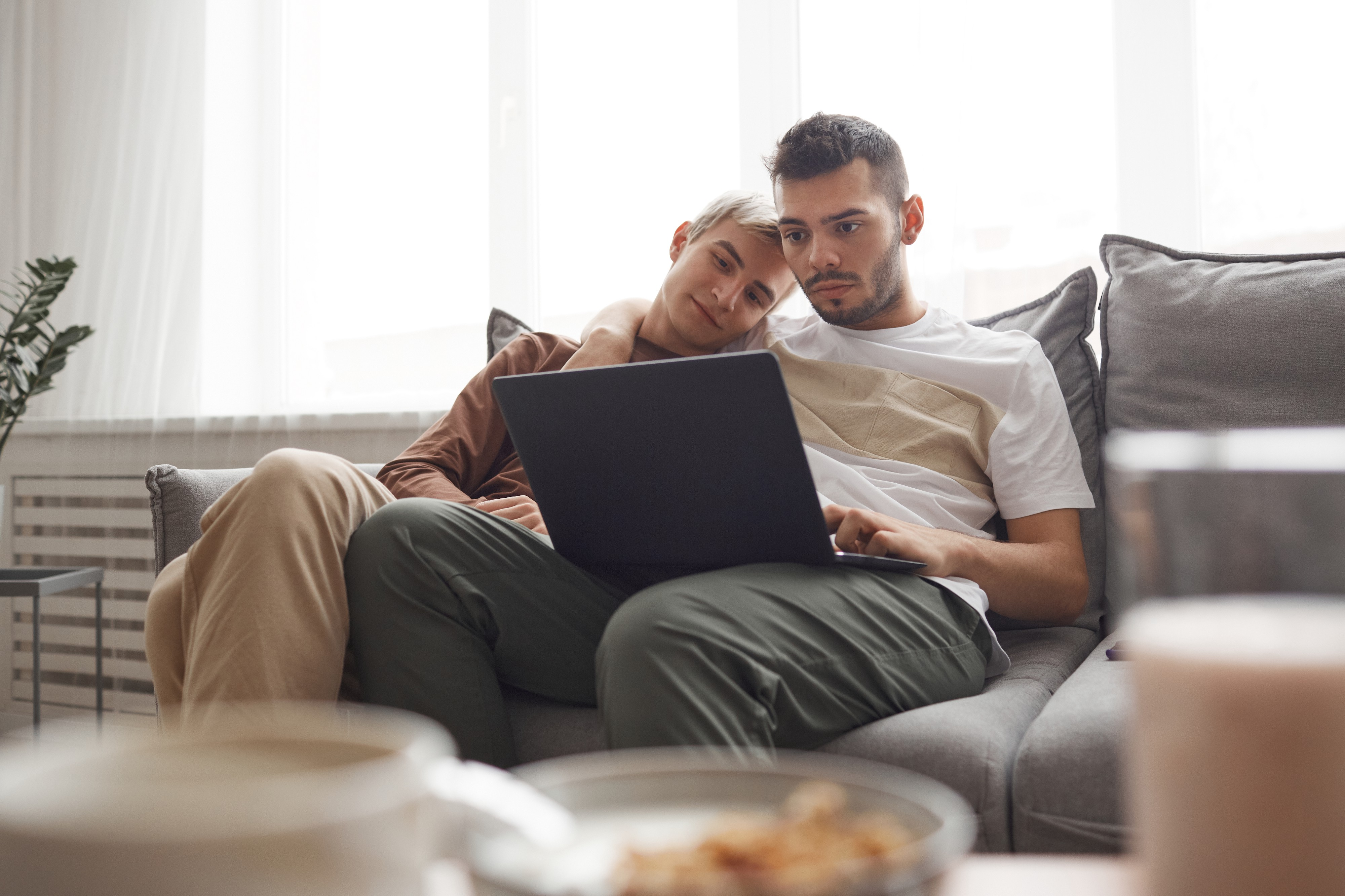 A couple embrace one another on the sofa and watch a movie on a laptop.