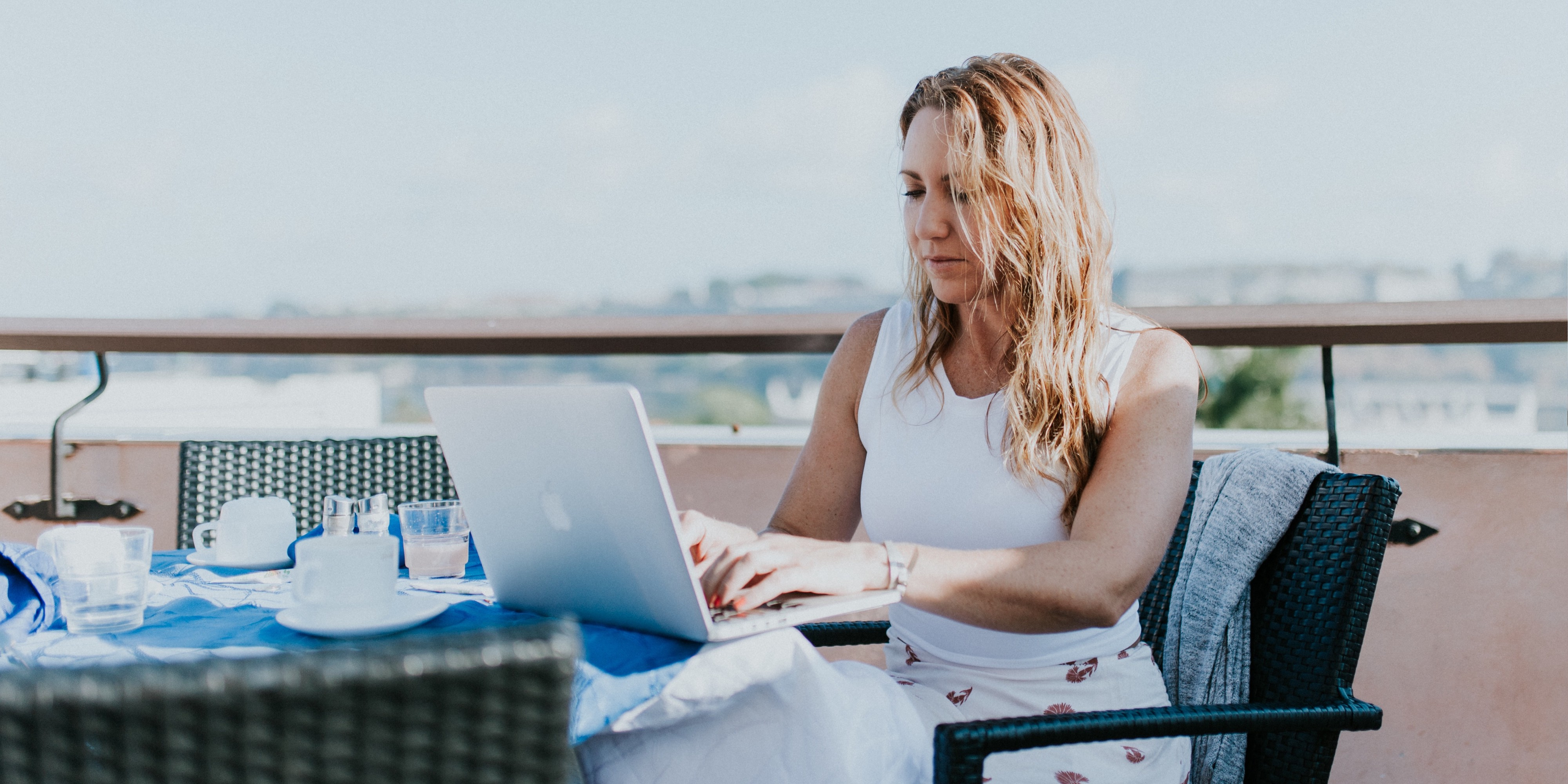 Image of a woman working on her laptop at a table on a balcony overlooking a cityscape