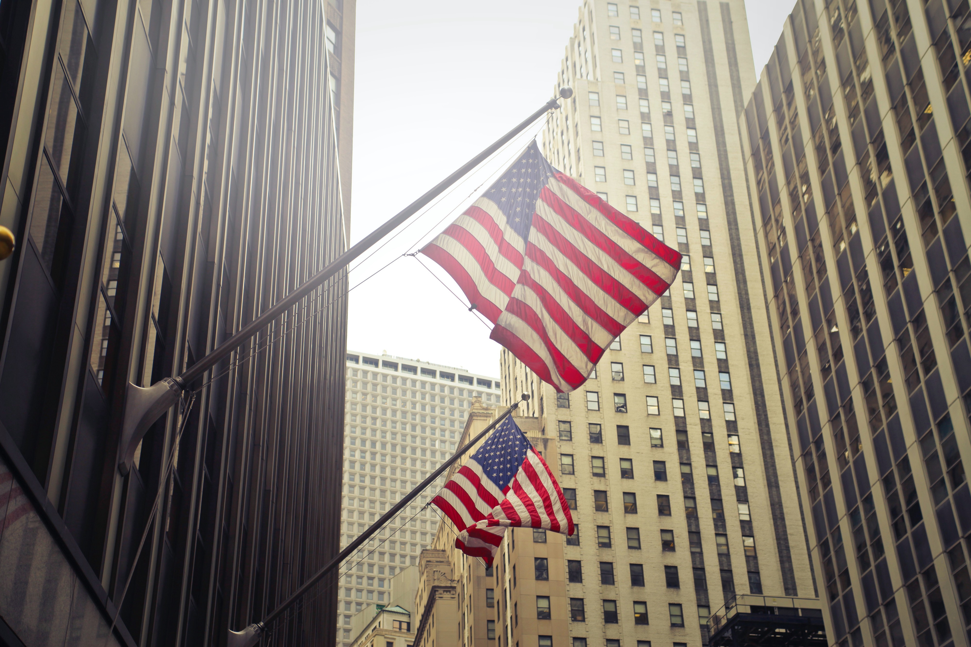 Two flags hang from poles coming off of large, corporate buildings.