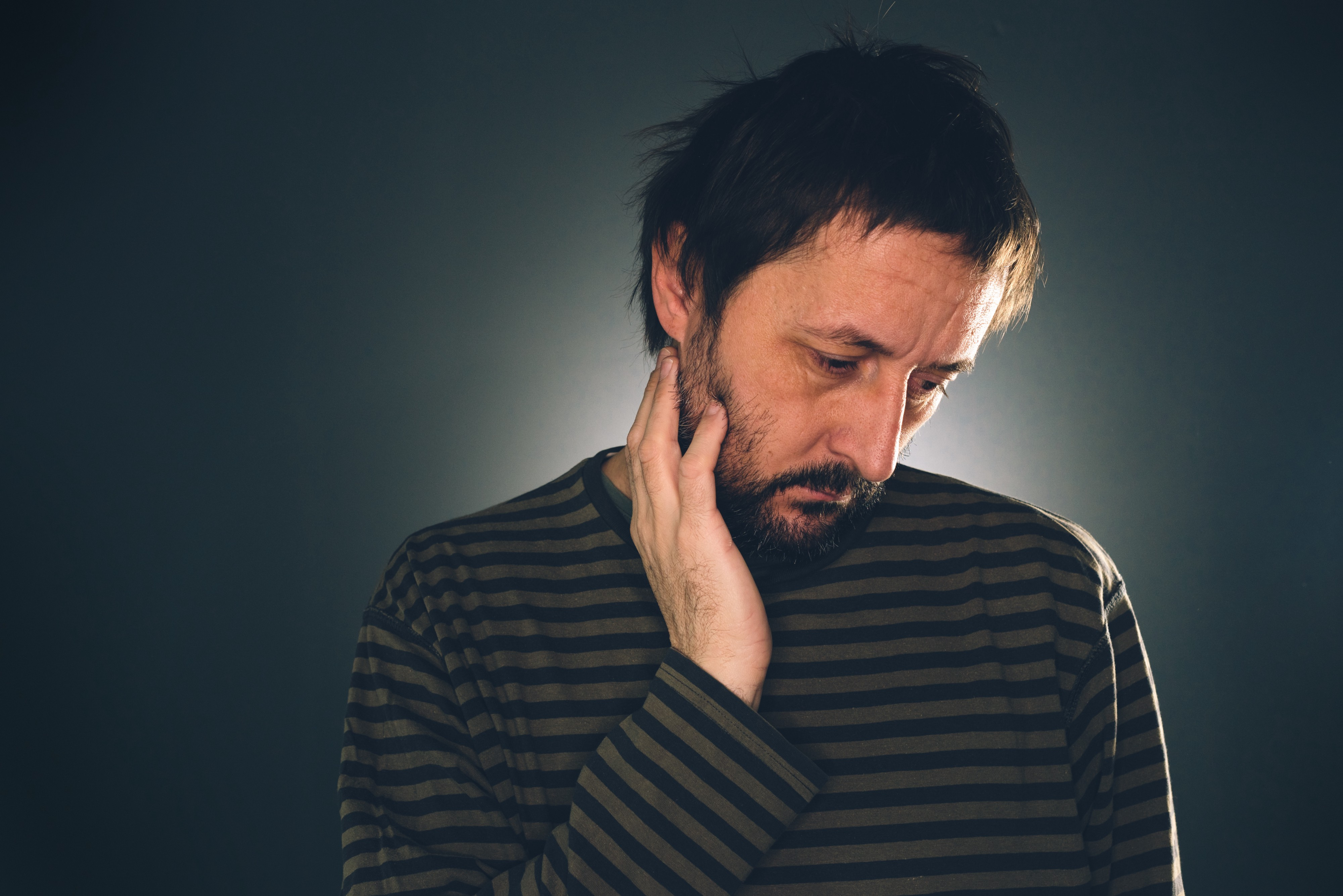 A depressed man hangs his head sadly while thinking intrusive thoughts.