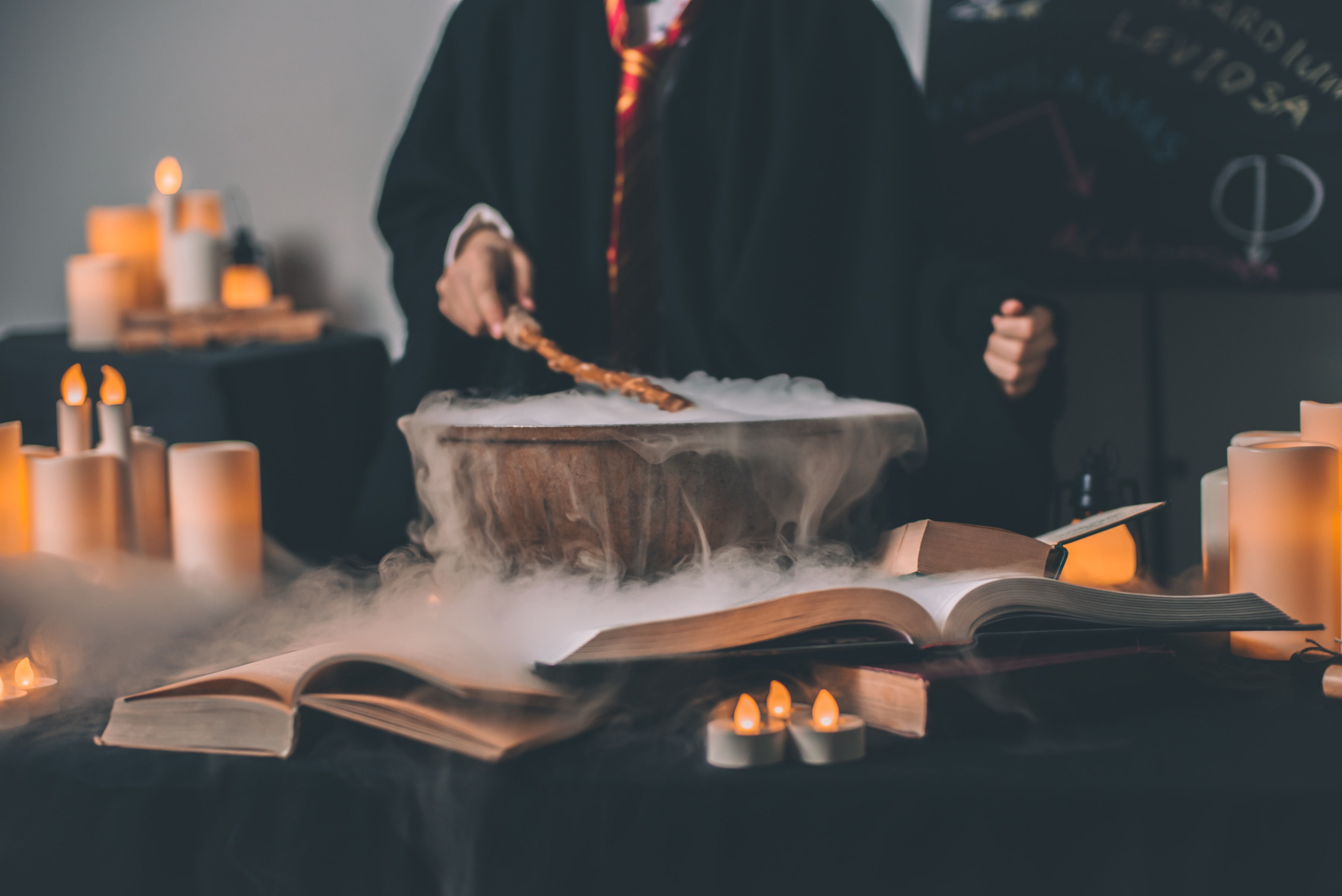 Title image: Photo of a wizard casting a spell over a smokey cauldron with books and candles around it.