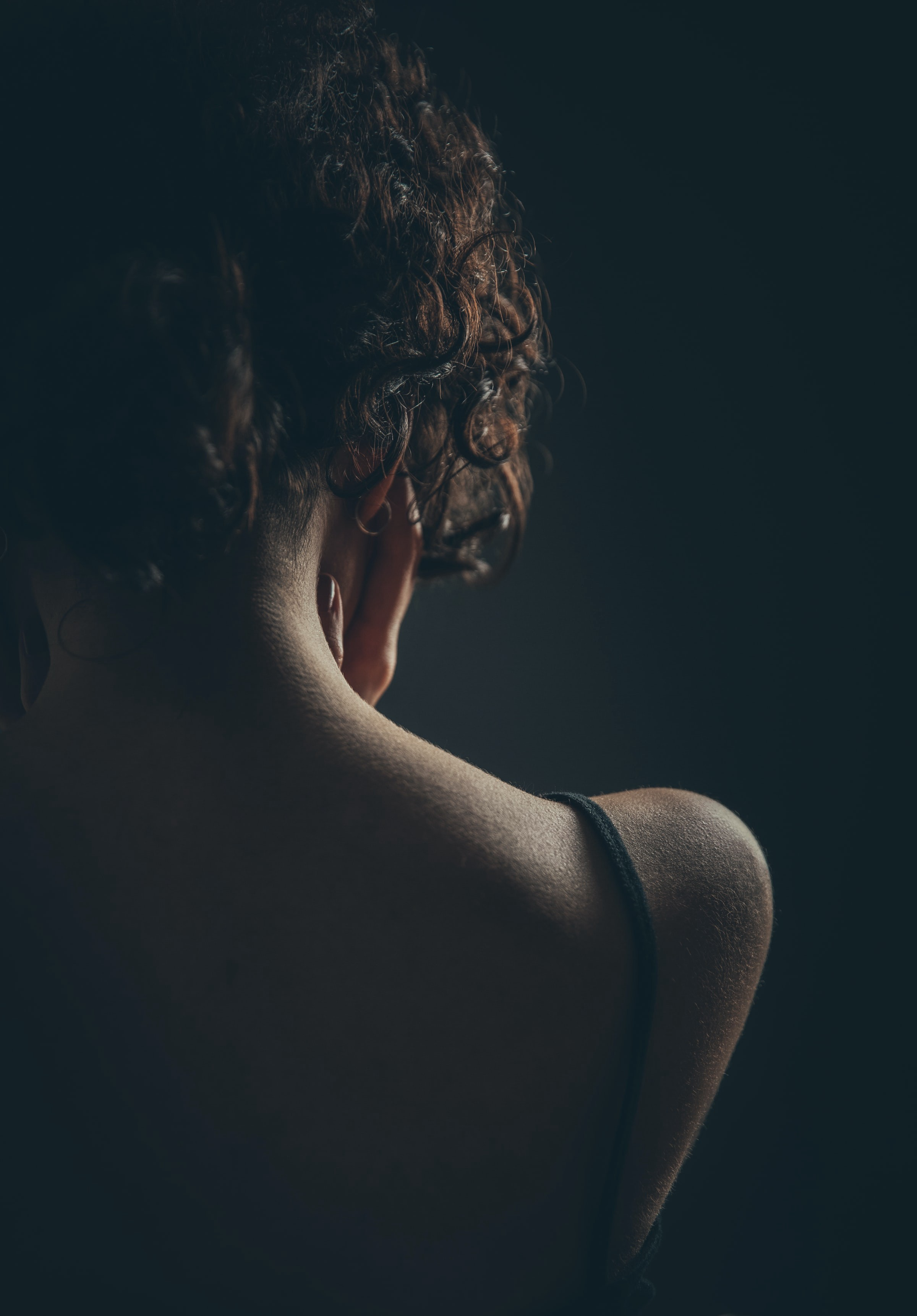 Curly haired woman viewed from over her shoulder, cupping her face in her hands.