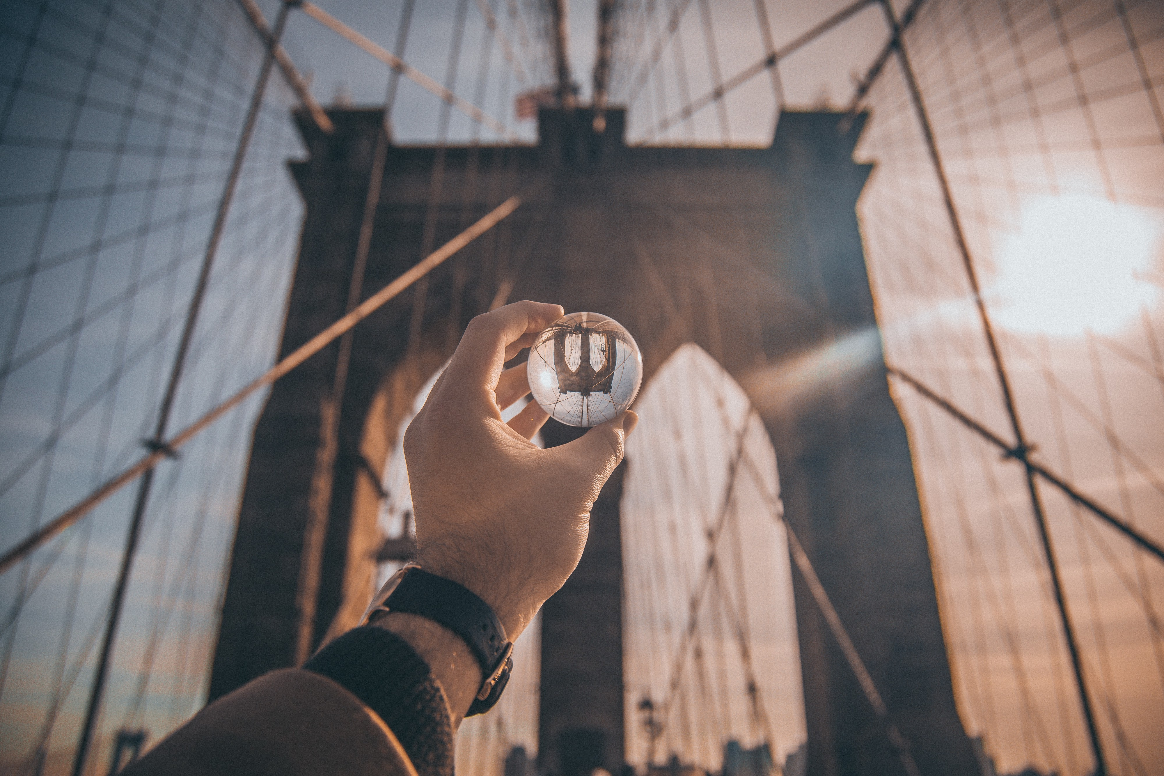 Hand holding glass ball up to the Brooklyn bridge. Glass ball shows bridge reflection but reversed.