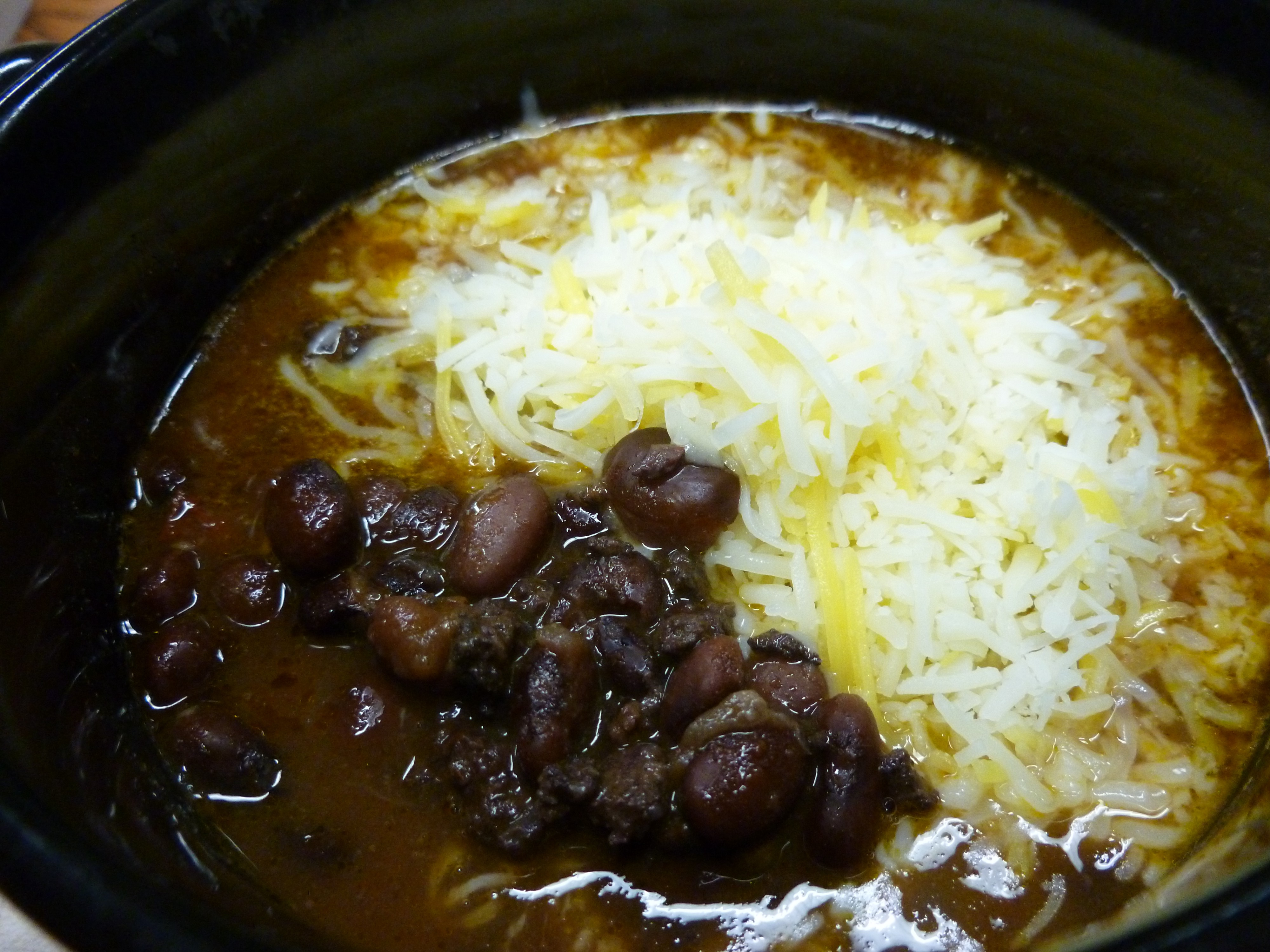 Black bean and ground elk chili with shredded cheese in a black bowl.