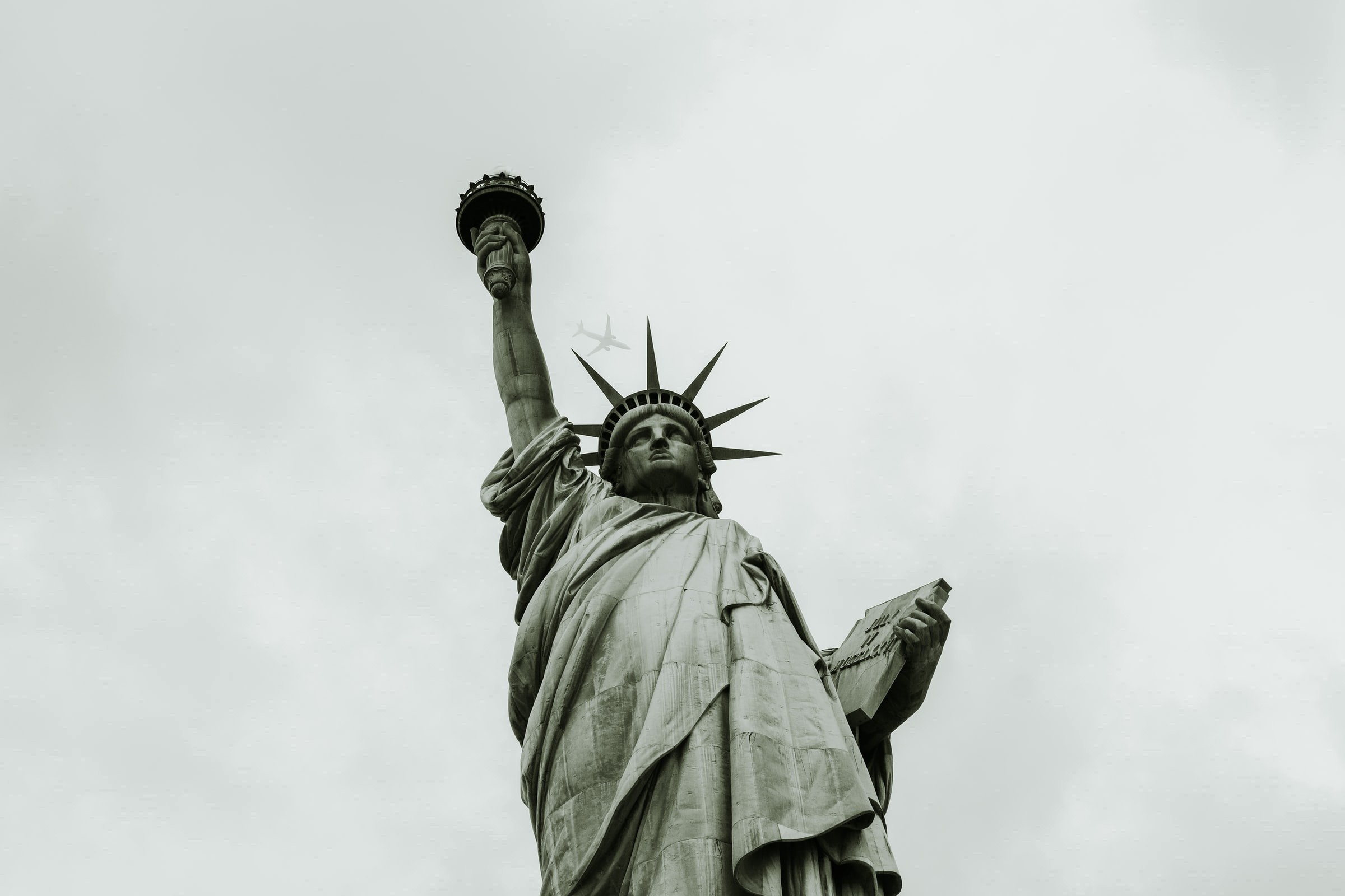 Black and White or Sepia color looking upward at the statue of liberty in America.