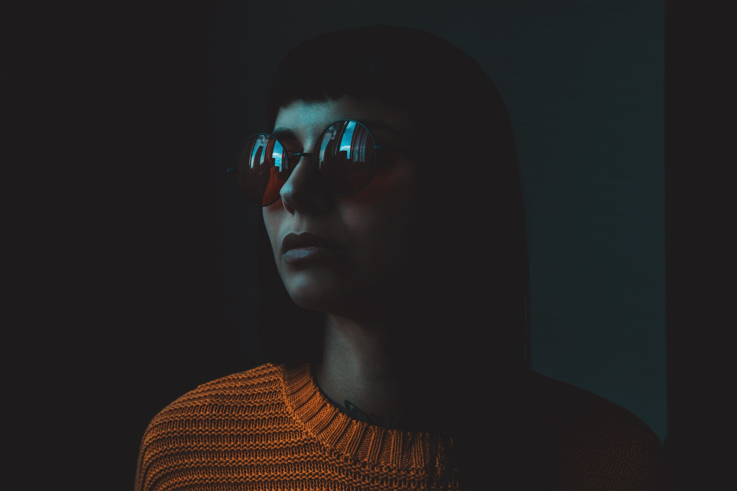 Portrait of a person—wearing a bob haircut, big dark sunglasses, and an orange knitted sweater—looking to the left side of the image in a very dark space. Reflected in the sunglasses is an open window showing a sliver of blue sky on each lens.