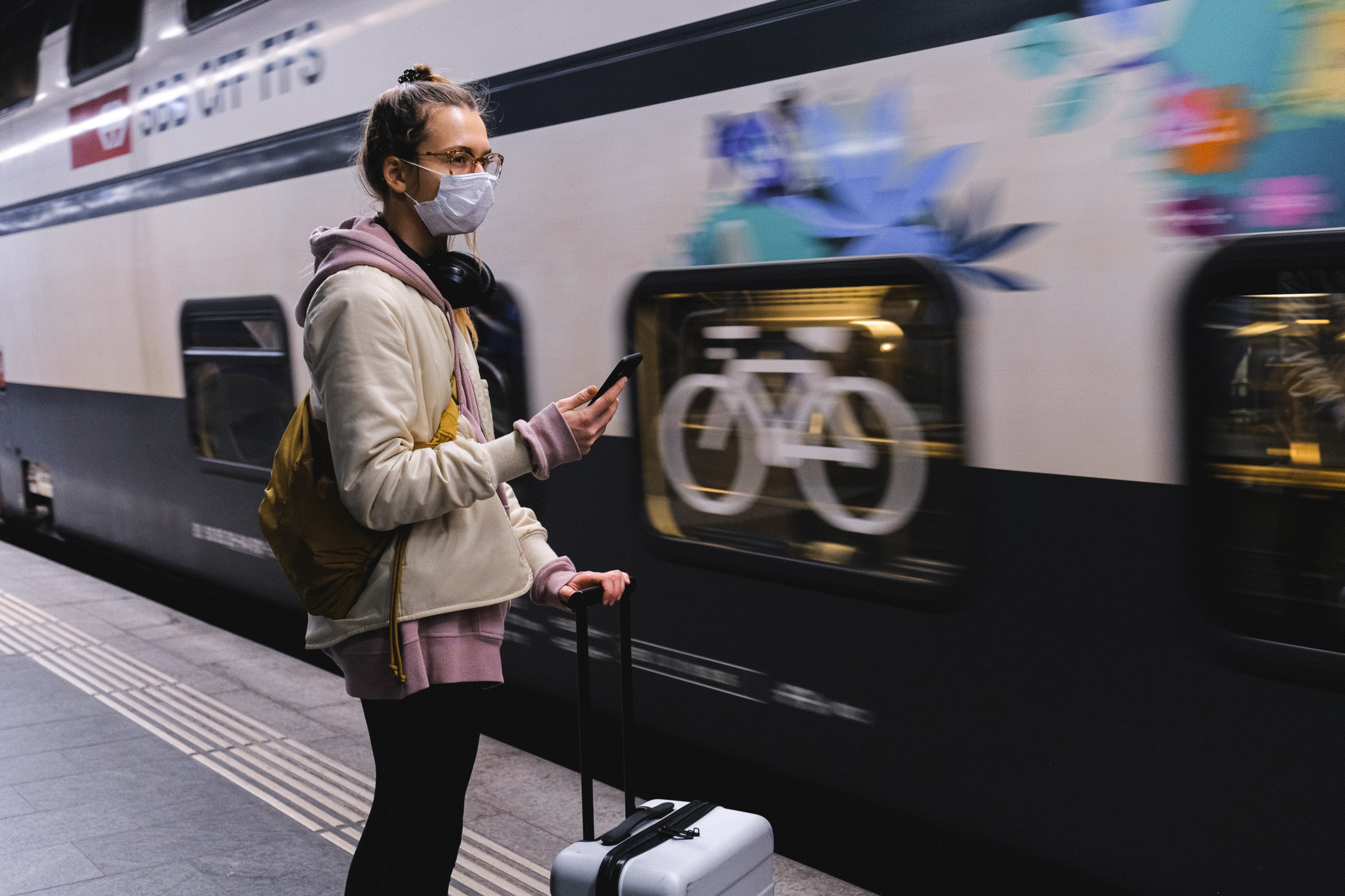 A girl with face mask standing in front of a moving train