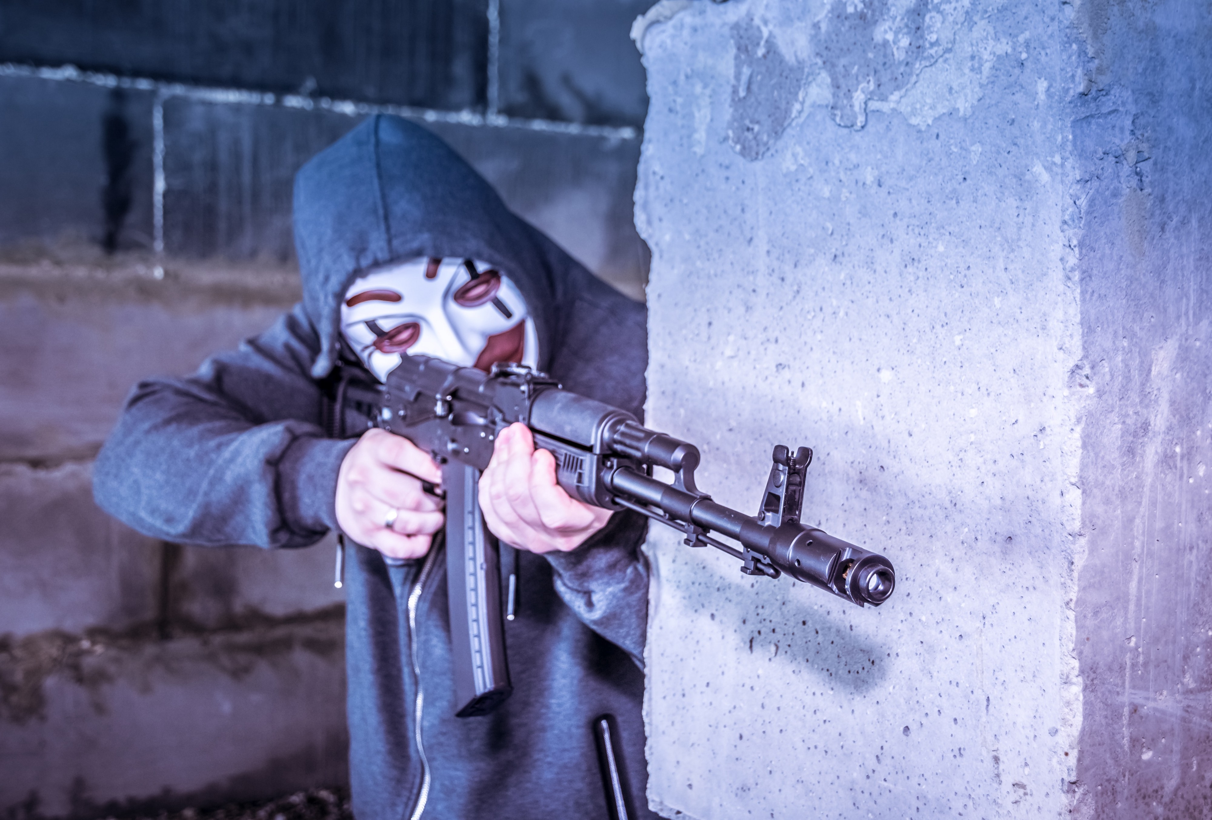 Man in joker mask aiming for gun shot from behind a wall.