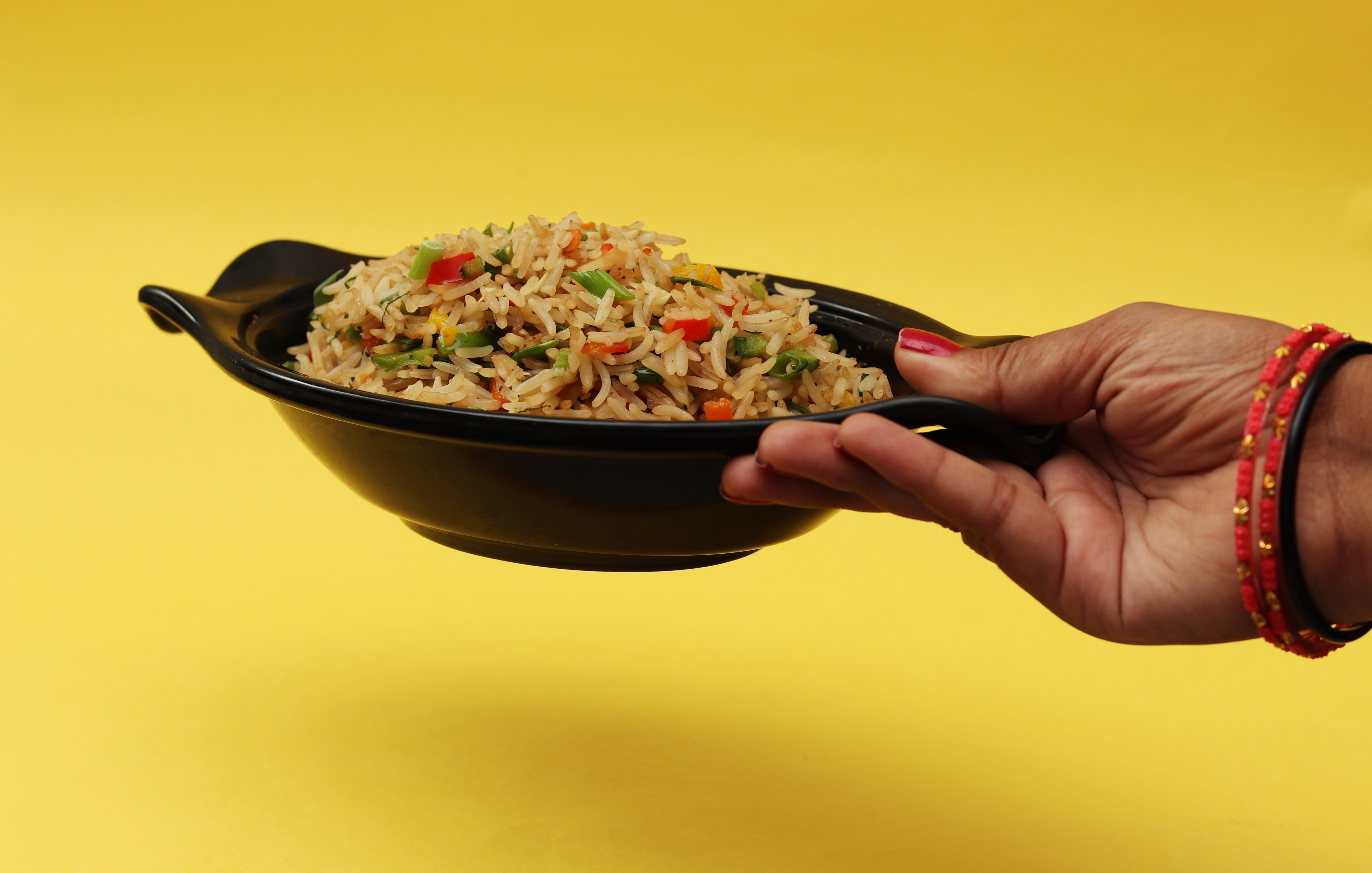 Woman's hand holding a bowl of fried rice