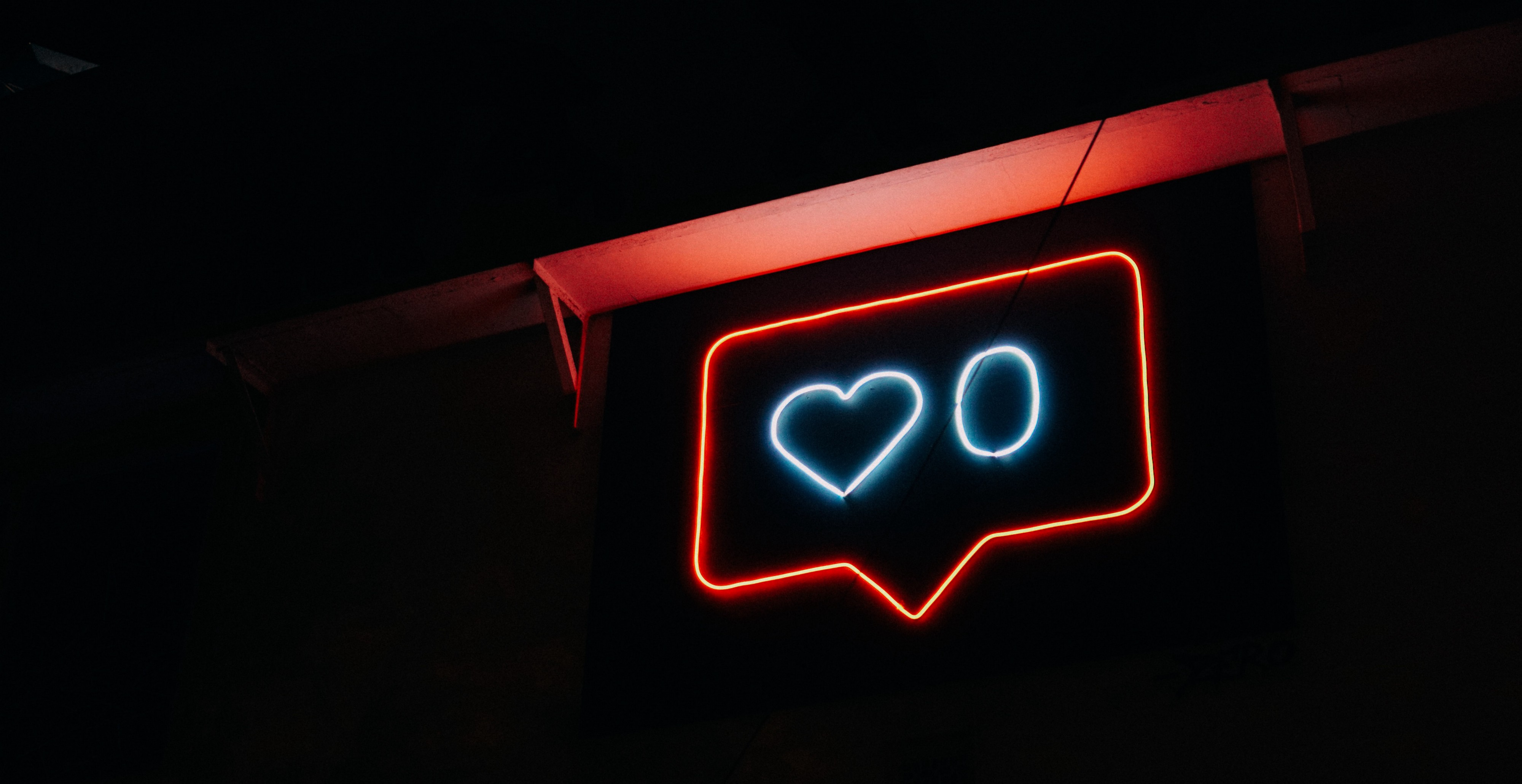 A neon light in the shape of a like button glows in a dark room.