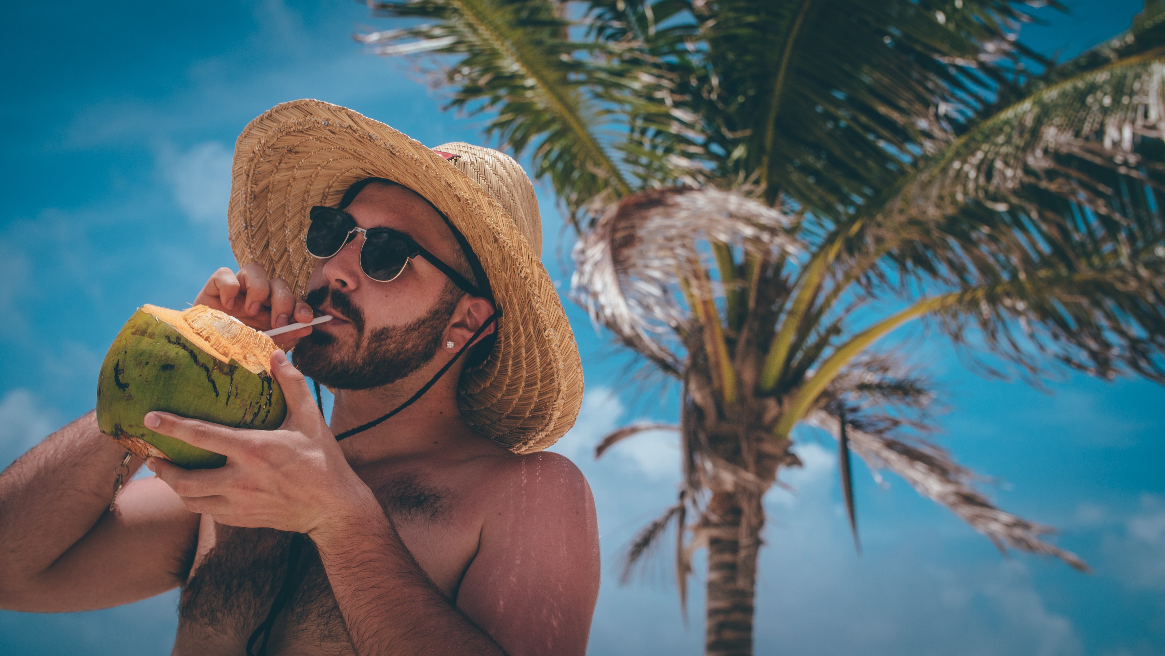 Man with hat on the beach in the sunshine drinking juice from coconut with coconut tree behind him